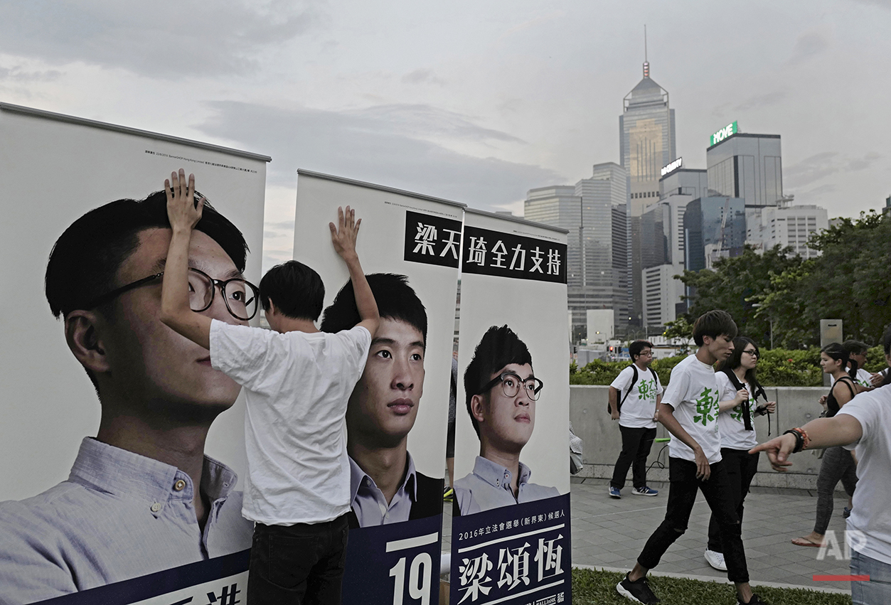 In this Aug. 28, 2016 photo, a supporter holds on to election banners for radical localist group Youngspiration's candidate Baggio Leung, center, during a pre-election rally in Hong Kong. (AP Photo/Vincent Yu)