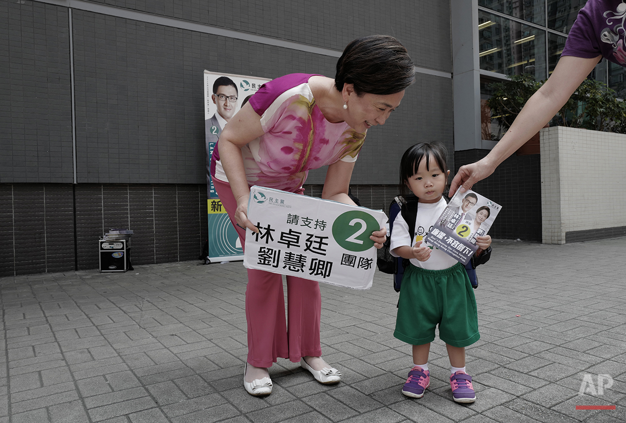 In this Wednesday, Aug. 24, 2016 photo, Hong Kong pro-democracy lawmaker, Emily Lau talks to a girl during a election campaign in Hong Kong. After two decades as a pro-democracy lawmaker, Emily Lau expects to step down as she and other party veterans give priority on the ballot to the party's younger faces. Two years after the end of chaotic pro-democracy protests in Hong Kong, a number of young activists who were politically awakened by the movement hope to keep its spirit alive by running for political office on Sunday, Sept. 4, 2016. (AP Photo/Vincent Yu)