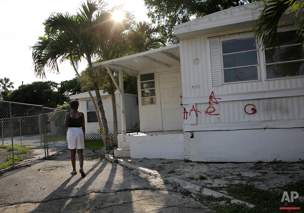 """In this Monday, June 13, 2016 photo, Clairmise Blanc, 72, walks through the Little Farm trailer park in El Portal, Fla. Blanc, 72, was known as the """"mayor of Little Farm"""" for keeping a log on the goings on at the 15-acre neighborhood. Residents, many of whom had owned their mobile homes in this close-knit community for years, were evicted in July after the park was purchased in 2015 by Wealthy Delight LLC. The site is now in preliminary planning for mixed use development. (AP Photo/Lynne Sladky)See these photos on  APImages.com"""