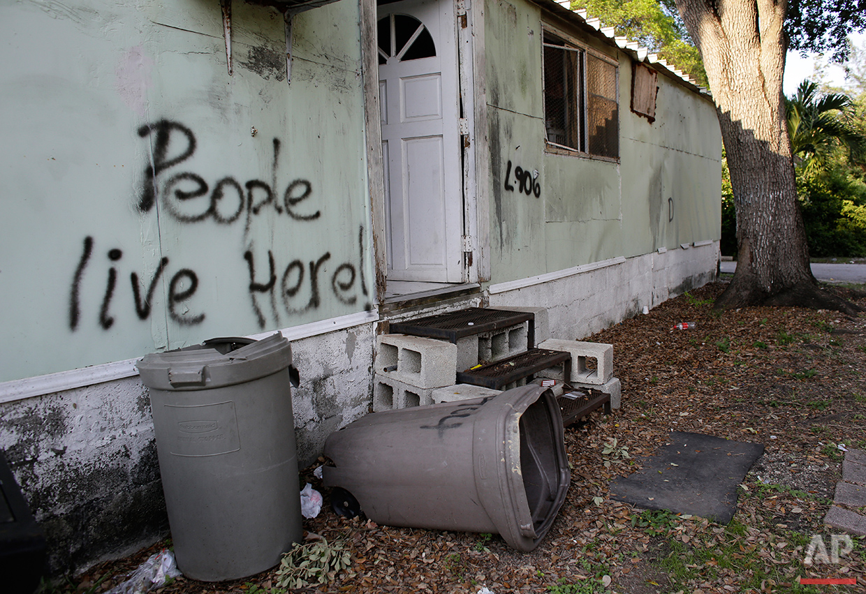 In this Monday, June 13, 2016 photo, graffiti is written on the side of a mobile home at the Little Farm trailer park in El Portal, Fla. In a city known for its glitzy, luxurious condo towers, affordable rental housing is hard to come by. Residents, many of whom had owned their mobile homes in this close-knit community for years, were evicted in July after the park was purchased in 2015 by Wealthy Delight LLC. The site is now in preliminary planning for mixed use development. (AP Photo/Lynne Sladky)See these photos on  APImages.com