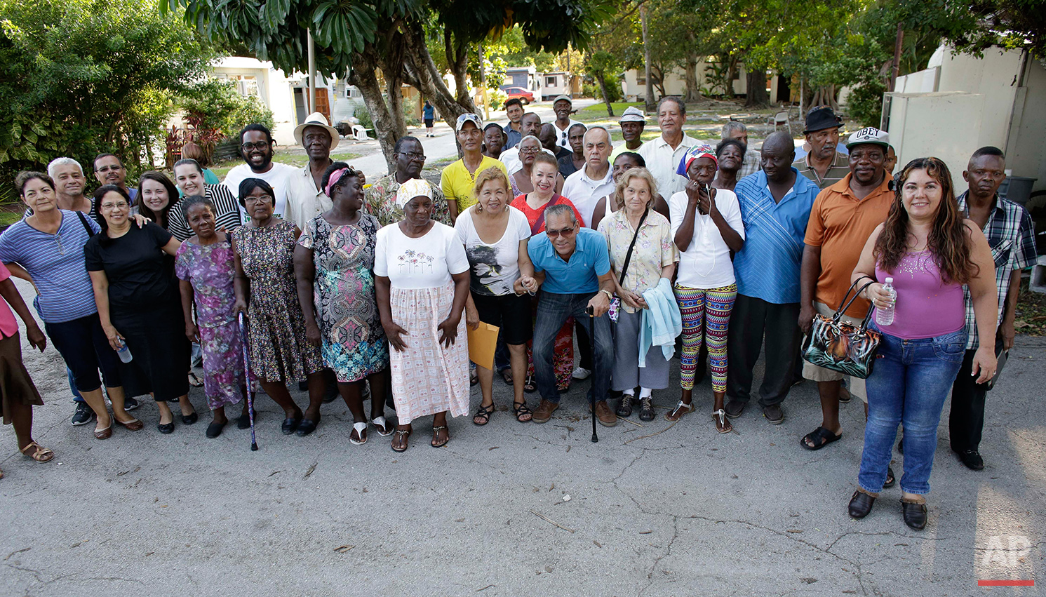 In this Tuesday, June 14, 2016 photo, residents of the Little Farm trailer park pose for a group photo in El Portal, Fla. The 15-acre neighborhood was home to a close-knit community until the site was purchased by Wealthy Delight LLC, and residents were evicted. The area is in preliminary planning for mixed use development. (AP Photo/Lynne Sladky)See these photos on  APImages.com
