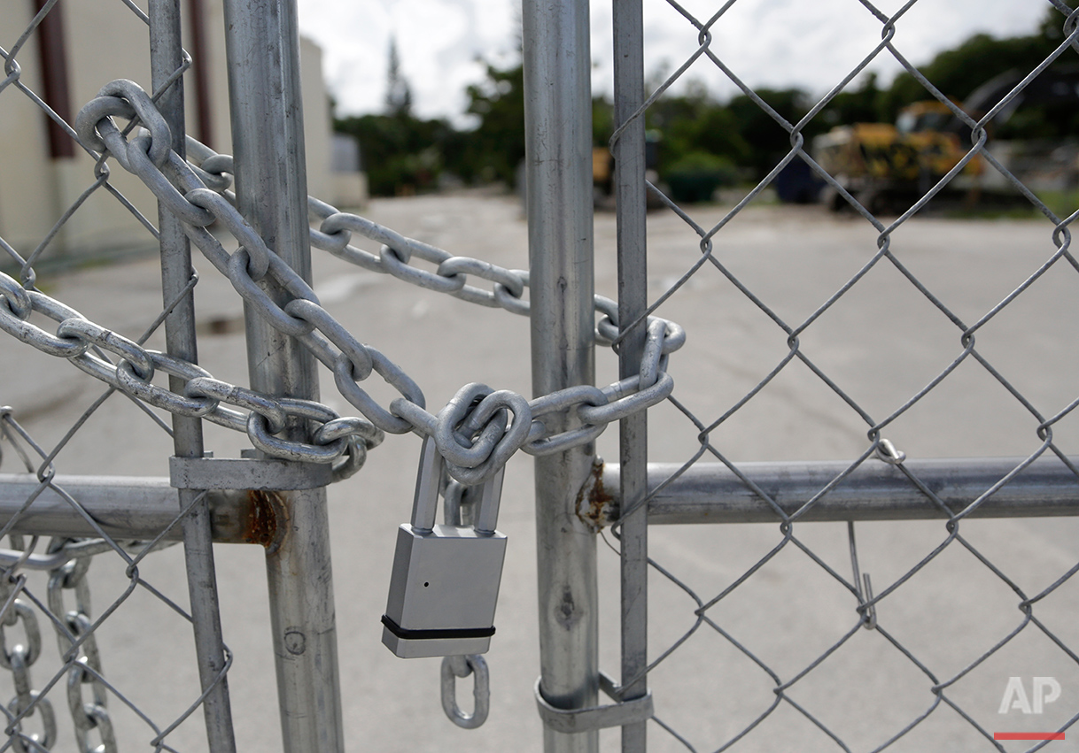 In this Monday, Aug. 29, 2016 photo, a padlock secures a fence blocking entry to the Little Farm trailer park in El Portal, Fla. Residents, many of whom had owned their mobile homes in this close-knit community for years, were evicted in July after the park was purchased in 2015 by Wealthy Delight LLC. The site is now in preliminary planning for mixed use development. (AP Photo/Lynne Sladky)See these photos on  APImages.com