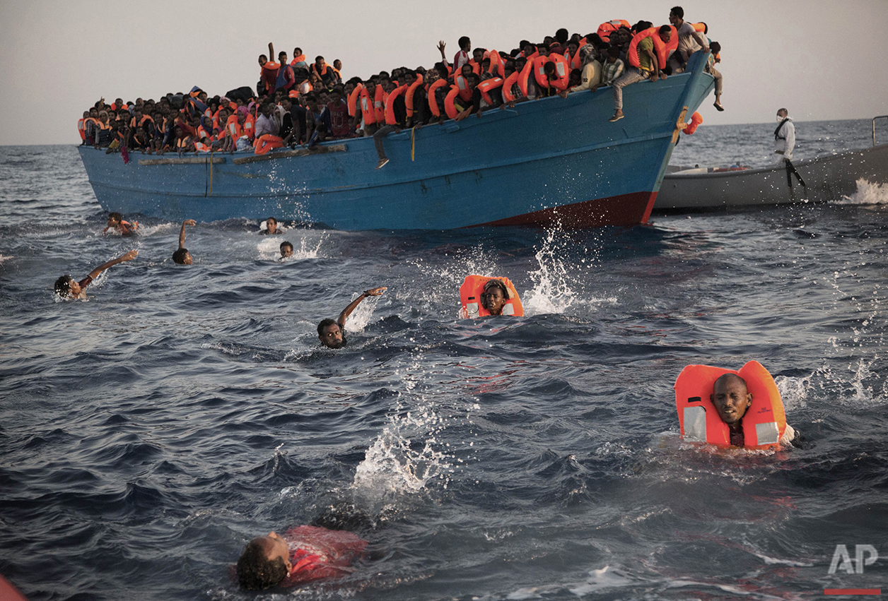 Migrants, most from Eritrea, jump into the water from a crowded wooden boat as they are helped by members of an NGO during a rescue operation in the Mediterranean sea, about 13 miles north of Sabratha, Libya, Monday, Aug. 29, 2016. Thousands were rescued Monday morning from more than 20 boats by members of the Proactiva Open Arms NGO before transferring them to the Italian cost guard and other NGO vessels operating in the zone. (AP Photo/Emilio Morenatti)
