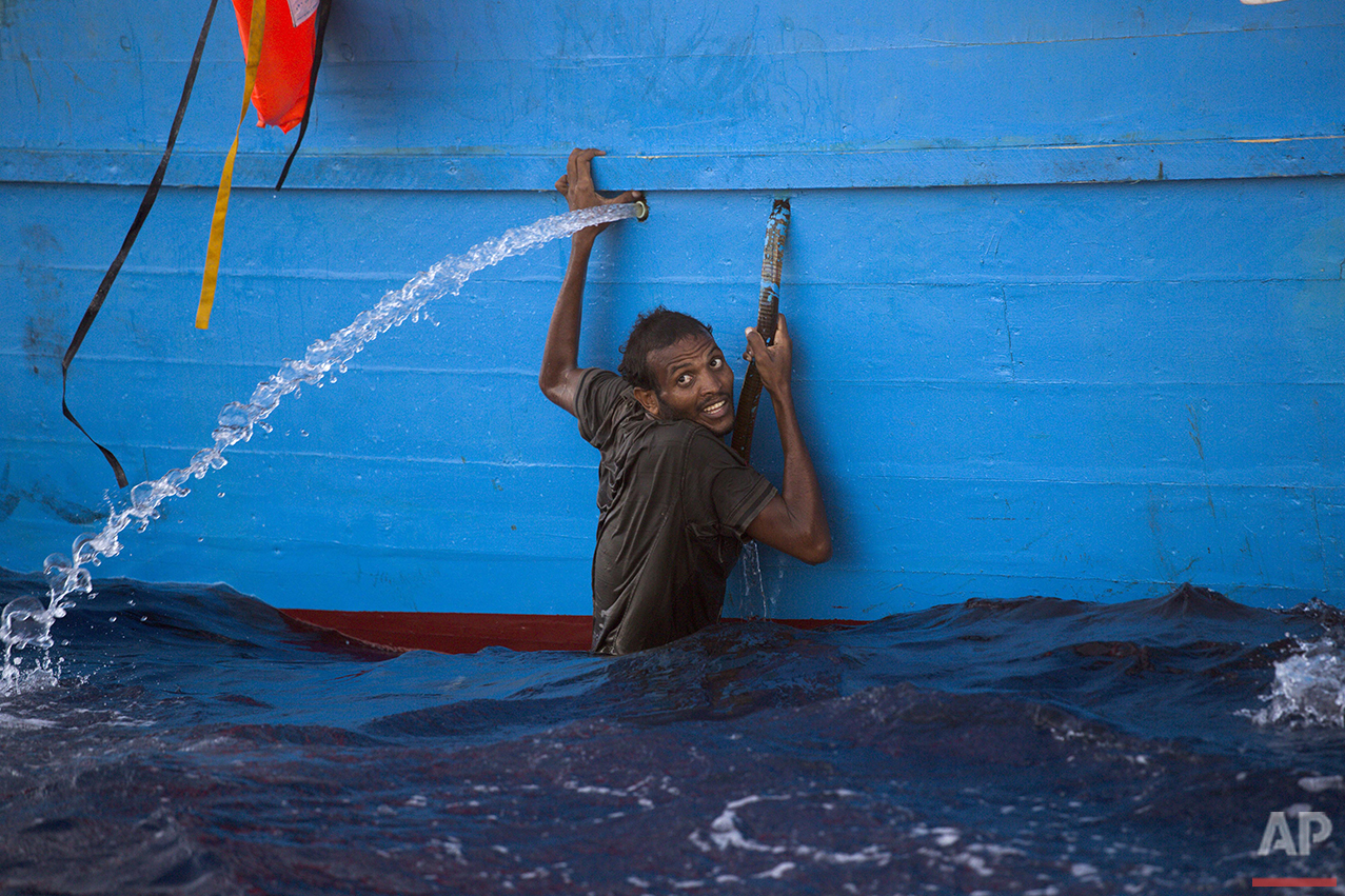 A man holds onto the side of a boat after jumping into the sea from a crowded wooden boat during a rescue operation in the Mediterranean sea, about 13 miles north of Sabratha, Libya, Monday, Aug. 29, 2016. Thousands of migrants and refugees were rescued Monday morning from more than 20 boats by members of Proactiva Open Arms NGO before transferring them to the Italian cost guard and other NGO vessels operating in the zone. (AP Photo/Emilio Morenatti)
