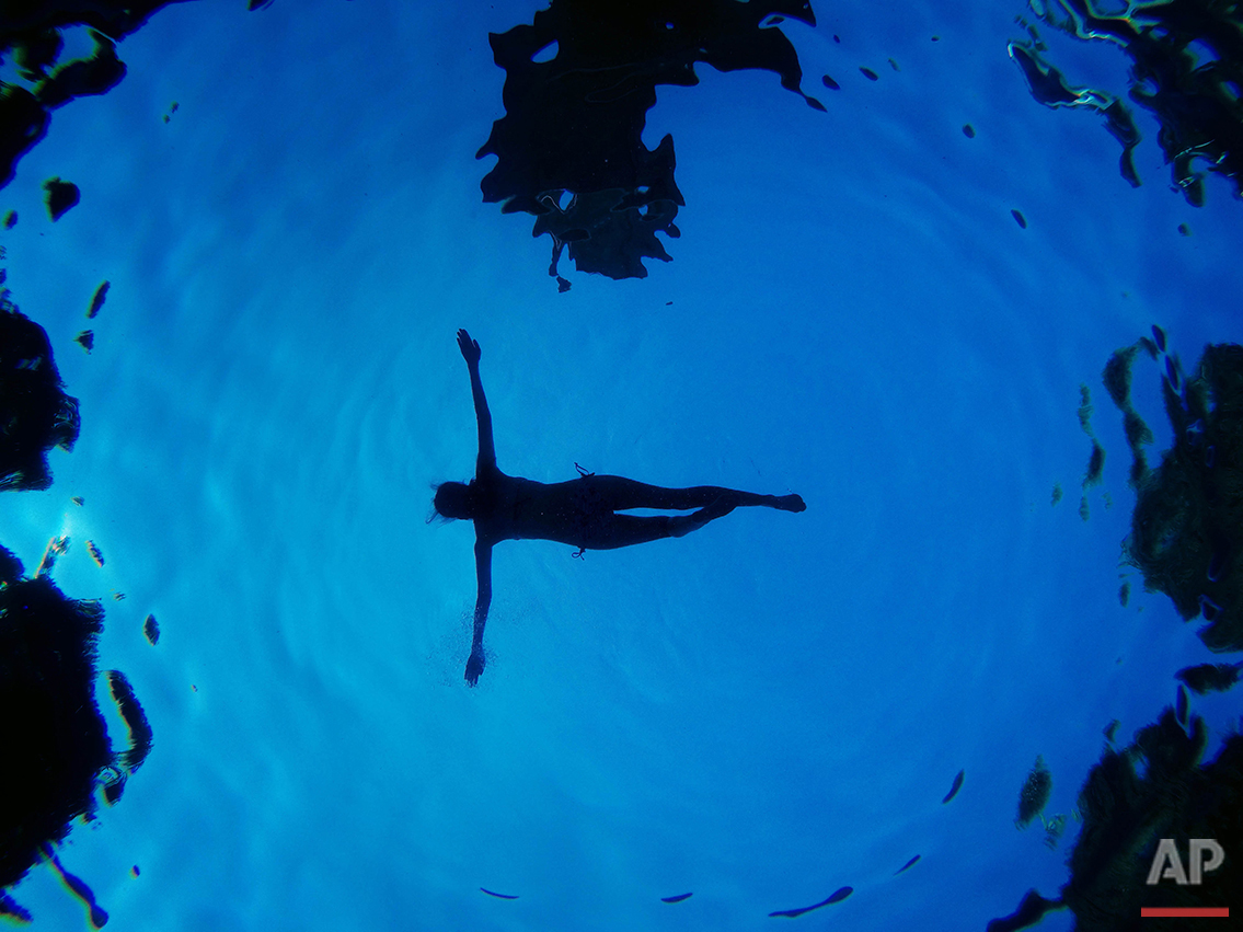 Seen from below, a woman floats in a swimming pool during a summer day in Madrid, Sunday, Aug. 28, 2016. (AP Photo/Daniel Ochoa de Olza)