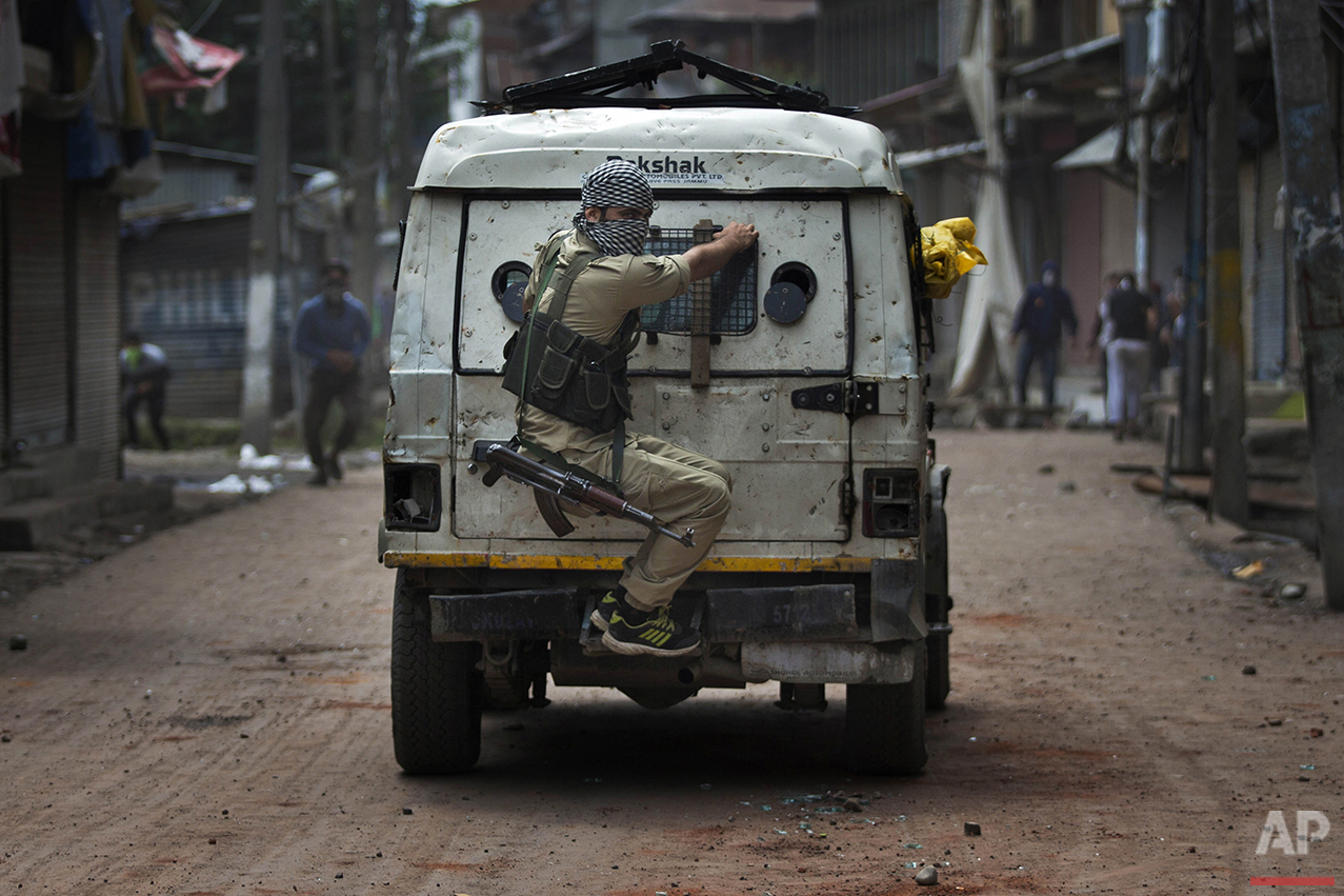 An Indian police officer takes cover behind an armored vehicle as Kashmiri protesters throw stones at him during a protest in Srinagar, Indian controlled Kashmir, Tuesday, Aug. 30, 2016. Clashes and a curfew continued in parts of Srinagar on Tuesday after anti-India protests and clashes erupted in several neighborhoods, a day after authorities lifted a curfew imposed in most parts of Indian-controlled Kashmir as part of a 52-day security lockdown. (AP Photo/Dar Yasin)