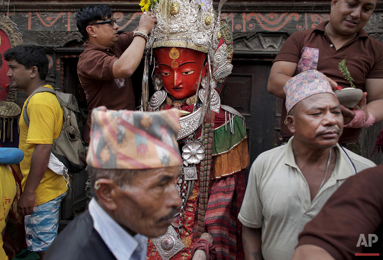 Worshipers gather around a statue of the Buddha during the Pancha Dan festival in Kathmandu, Nepal, Tuesday, Aug. 30, 2016. The festival of five summer gifts is when devotees donate five essential commodities necessary for living, including items such as rice, salt and money. (AP Photo/Niranjan Shrestha)