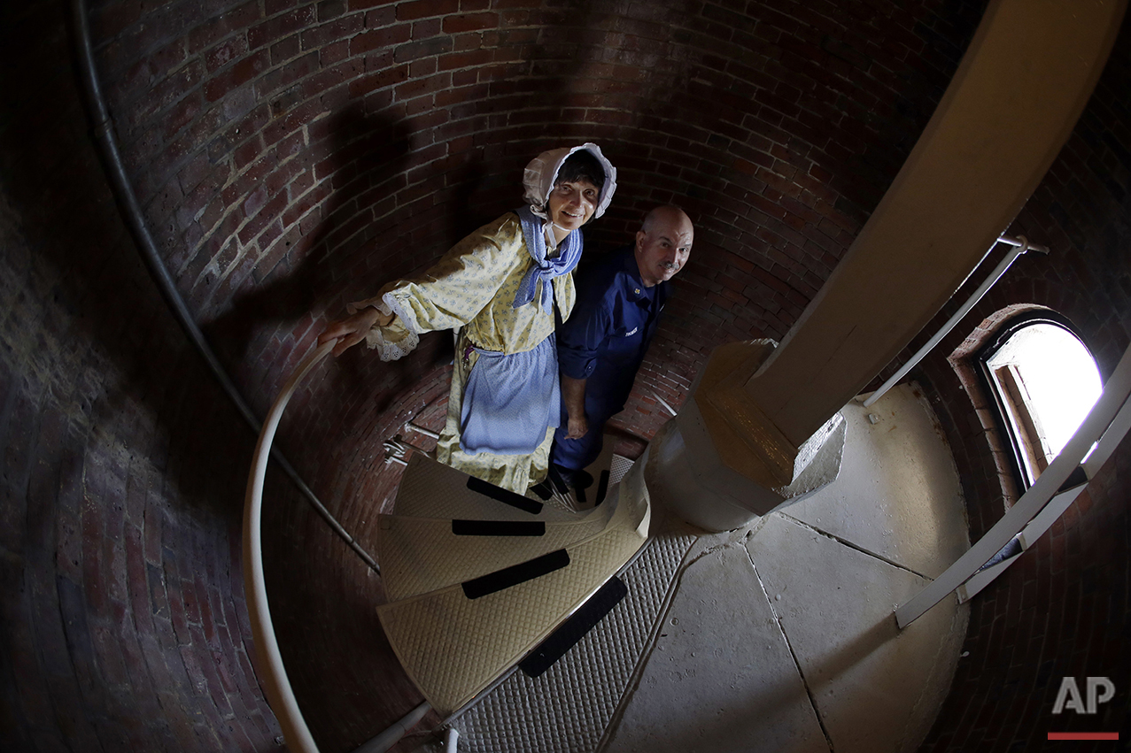 In this Aug. 17, 2016 photo, Sally Snowman, the keeper of Boston Light, and her husband, Jay Thomson of the Auxiliary Coast Guard, climb down the steps inside the lighthouse on Little Brewster Island in Boston Harbor. (AP Photo/Elise Amendola)See these photos on  APImages.com