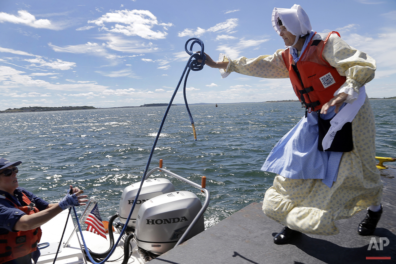 In this Aug. 17, 2016 photo, Sally Snowman, right, the keeper of Boston Light, tosses a line to Robin Young of the Auxiliary Coast Guard at the dock of Little Brewster Island in Boston Harbor. (AP Photo/Elise Amendola)See these photos on  APImages.com