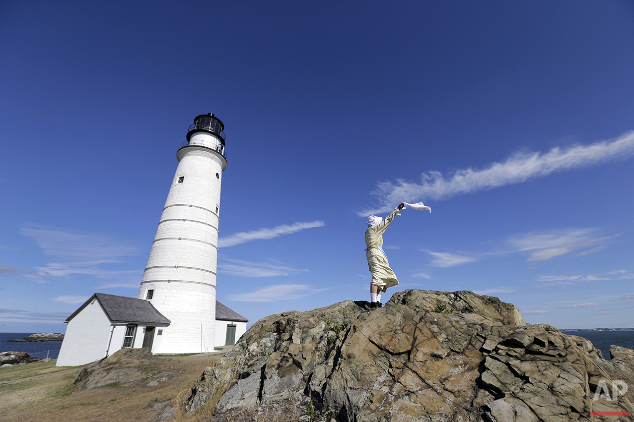 In this Aug. 17, 2016 photo, Sally Snowman, the keeper of Boston Light, waves a cloth from a rock outcrop on Little Brewster Island in Boston Harbor. (AP Photo/Elise Amendola)See these photos on  APImages.com