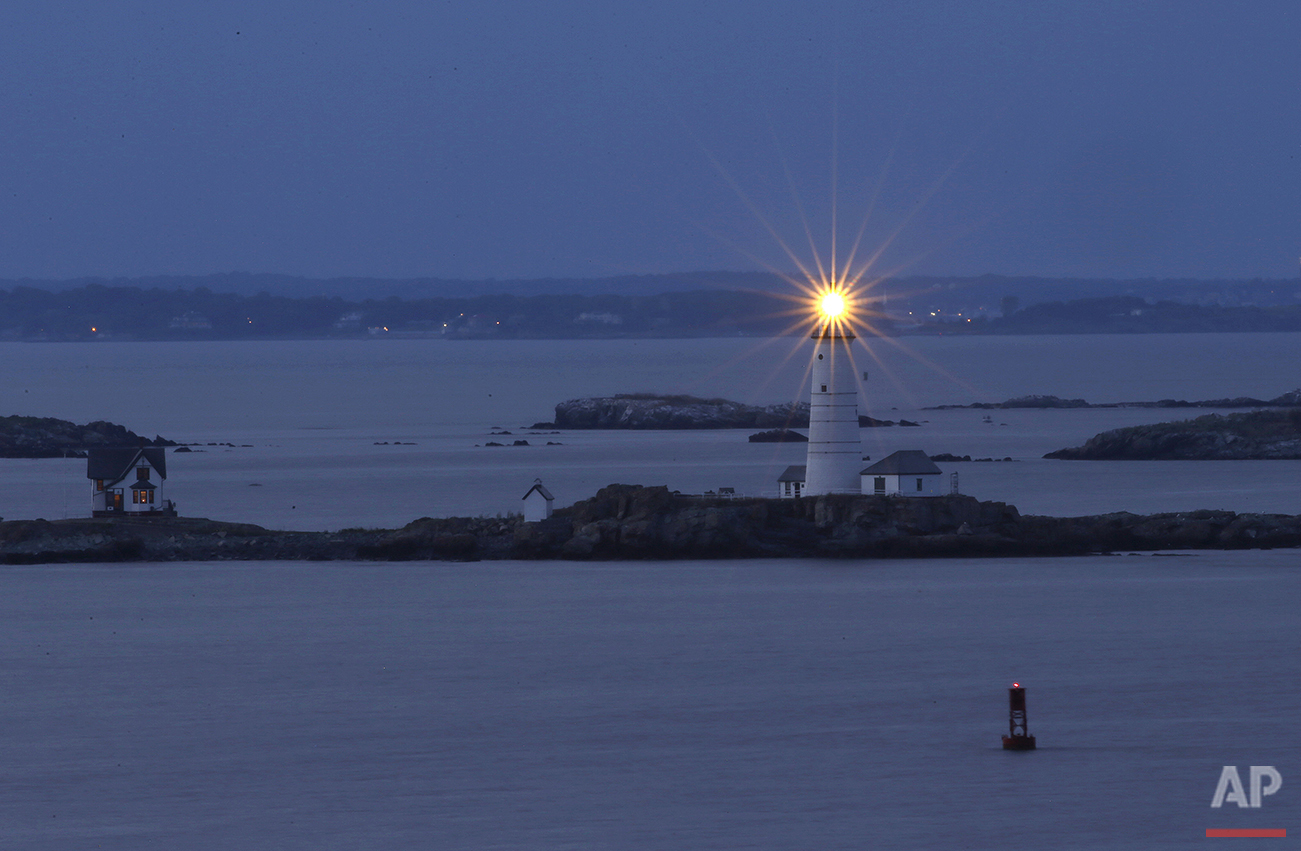 In this Aug. 25, 2016 photo, Boston Light, America's oldest lighthouse, flashes in Boston Harbor as seen from Hull, Mass. (AP Photo/Elise Amendola)See these photos on  APImages.com