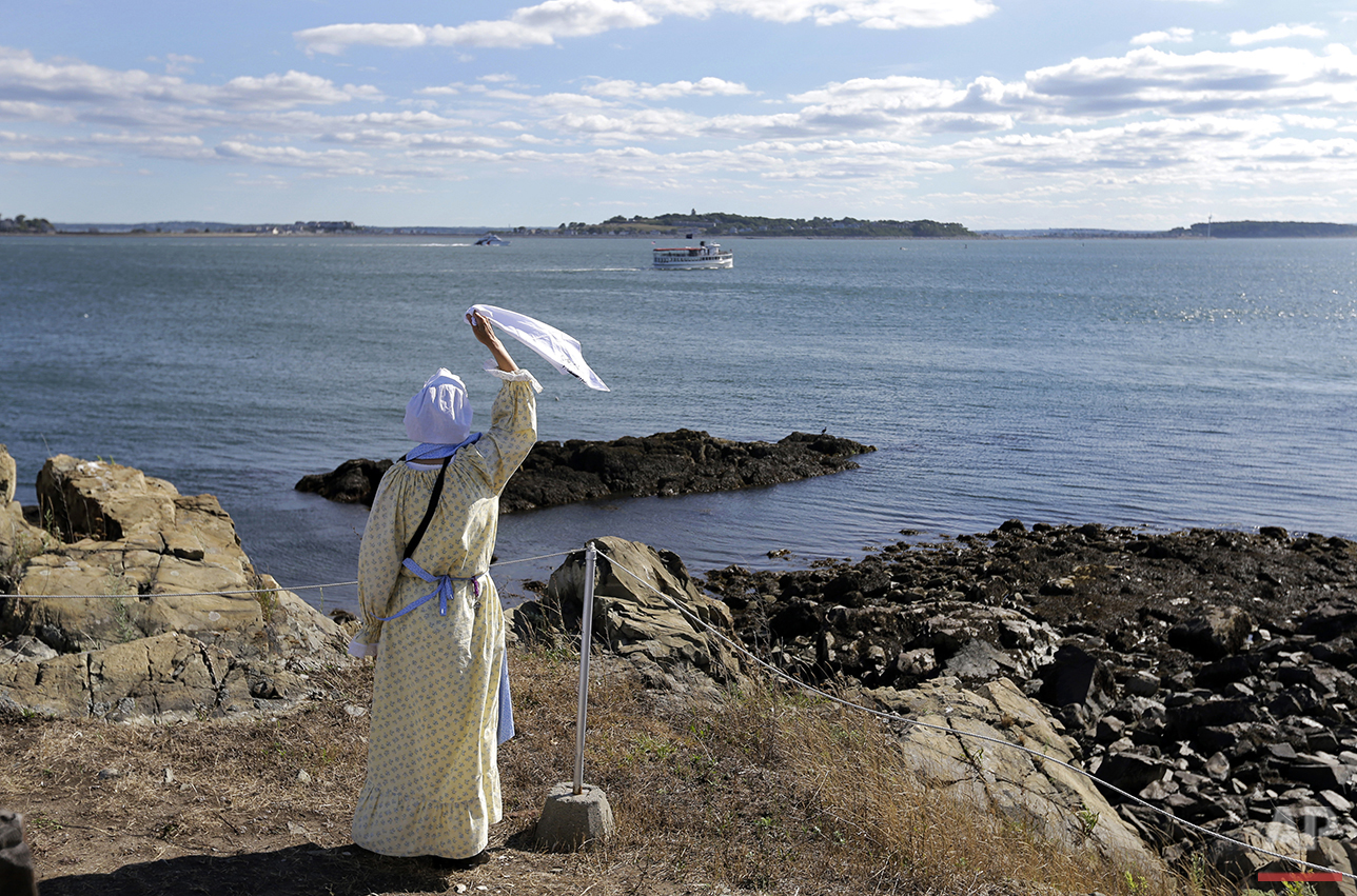 In this Aug. 17, 2016 photo, Sally Snowman, the keeper of Boston Light, waves to a cruise boat from Little Brewster Island in Boston Harbor. (AP Photo/Elise Amendola)See these photos on  APImages.com