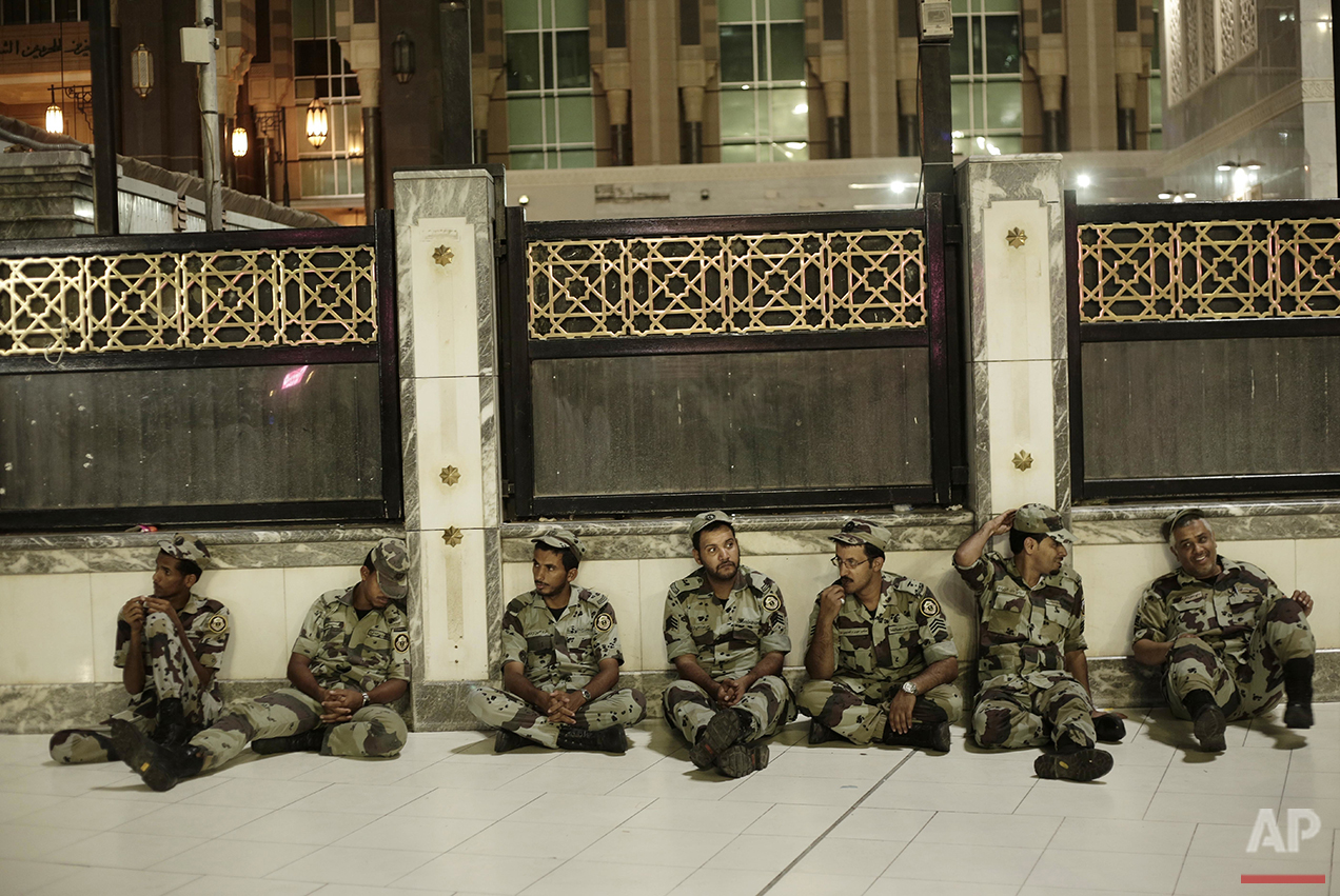 Saudi security rest before praying the Fajr, prayer before sunrise, outside the Grand Mosque in the Muslim holy city of Mecca, Saudi Arabia, Thursday, Sept. 8, 2016. Muslim pilgrims have begun arriving at the holiest sites in Islam ahead of the annual hajj pilgrimage in Saudi Arabia, with some weeping with their hands outstretched for a fleeting touch of the Kaaba. The cube-shaped shrine, at the center of Mecca's Grand Mosque, is the site the world's 1.6 billion Muslims pray toward five times a day. (AP Photo/Nariman El-Mofty)