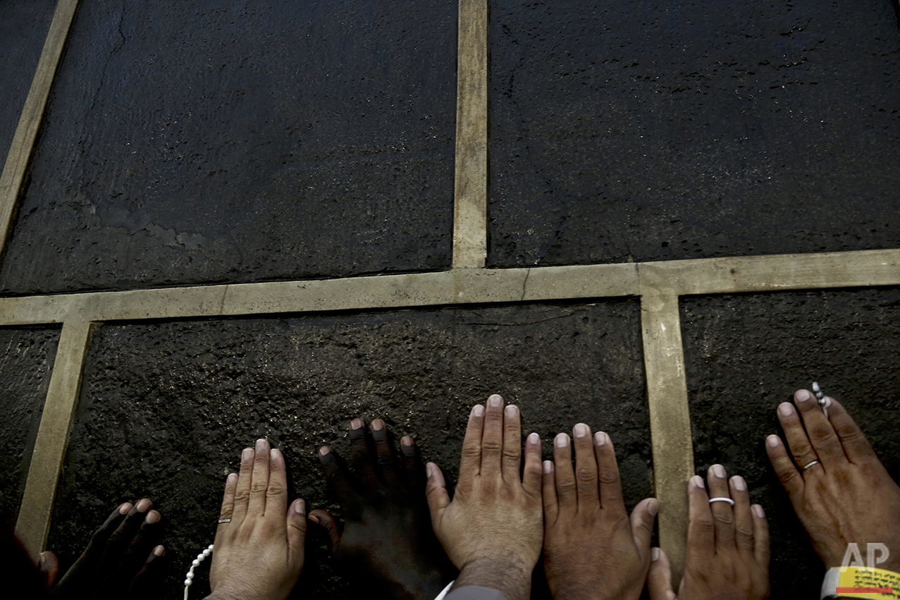 Muslim pilgrims reach the Kaaba, Islam's holiest shrine, to touch it for blessing at the Grand Mosque in the Muslim holy city of Mecca, Saudi Arabia, Wednesday, Sept. 7, 2016. Millions of pilgrims have arrived to Mecca ahead of the Hajj annual pilgrimage which begins Saturday, Sept. 10, 2016. (AP Photo/Nariman El-Mofty)