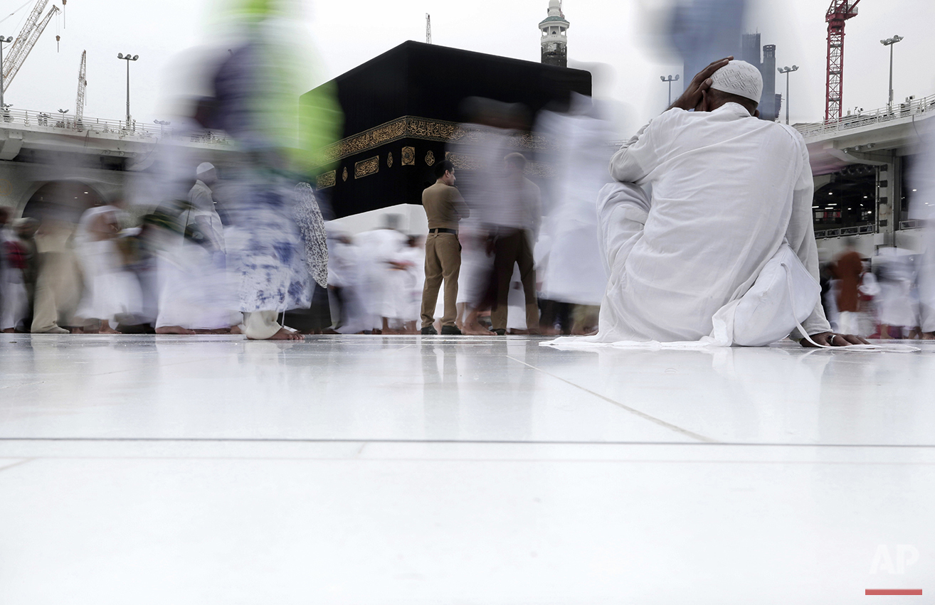 Saudi security stand guard as Muslim pilgrims circle the Kaaba, Islam's holiest shrine, at the Grand Mosque in the Muslim holy city of Mecca, Saudi Arabia, Thursday, Sept. 8, 2016. Millions of pilgrims have arrived to Mecca ahead of the Hajj annual pilgrimage which begins Saturday, Sept. 10, 2016. (AP Photo/Nariman El-Mofty)