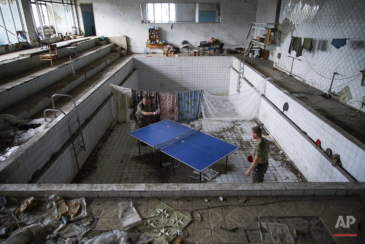 In this photo taken on Thursday, Aug. 25, 2016, Ukrainian soldiers play table tennis at a damaged swimming pool in the village of Marinka, near Donetsk, eastern Ukraine. More than 9,500 people have been killed in the fighting that began in April 2014, according to United Nations figures, but despite the carnage or the weariness of those inflicting it, there's little expectation it will actually stop anytime soon. (AP Photo/Max Black)See these photos on  APImages.com