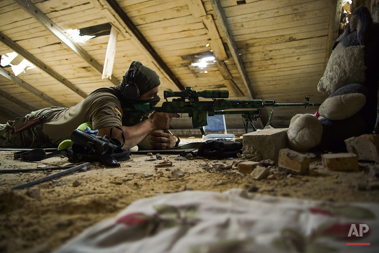 In this photo taken on Thursday, Aug. 25, 2016, a Ukrainian sniper who gave his name only as Corporal takes his position in the village of Marinka, near Donetsk, eastern Ukraine. More than 9,500 people have been killed in the fighting that began in April 2014, according to United Nations figures, but despite the carnage or the weariness of those inflicting it, there's little expectation it will actually stop anytime soon. (AP Photo/Max Black)See these photos on  APImages.com