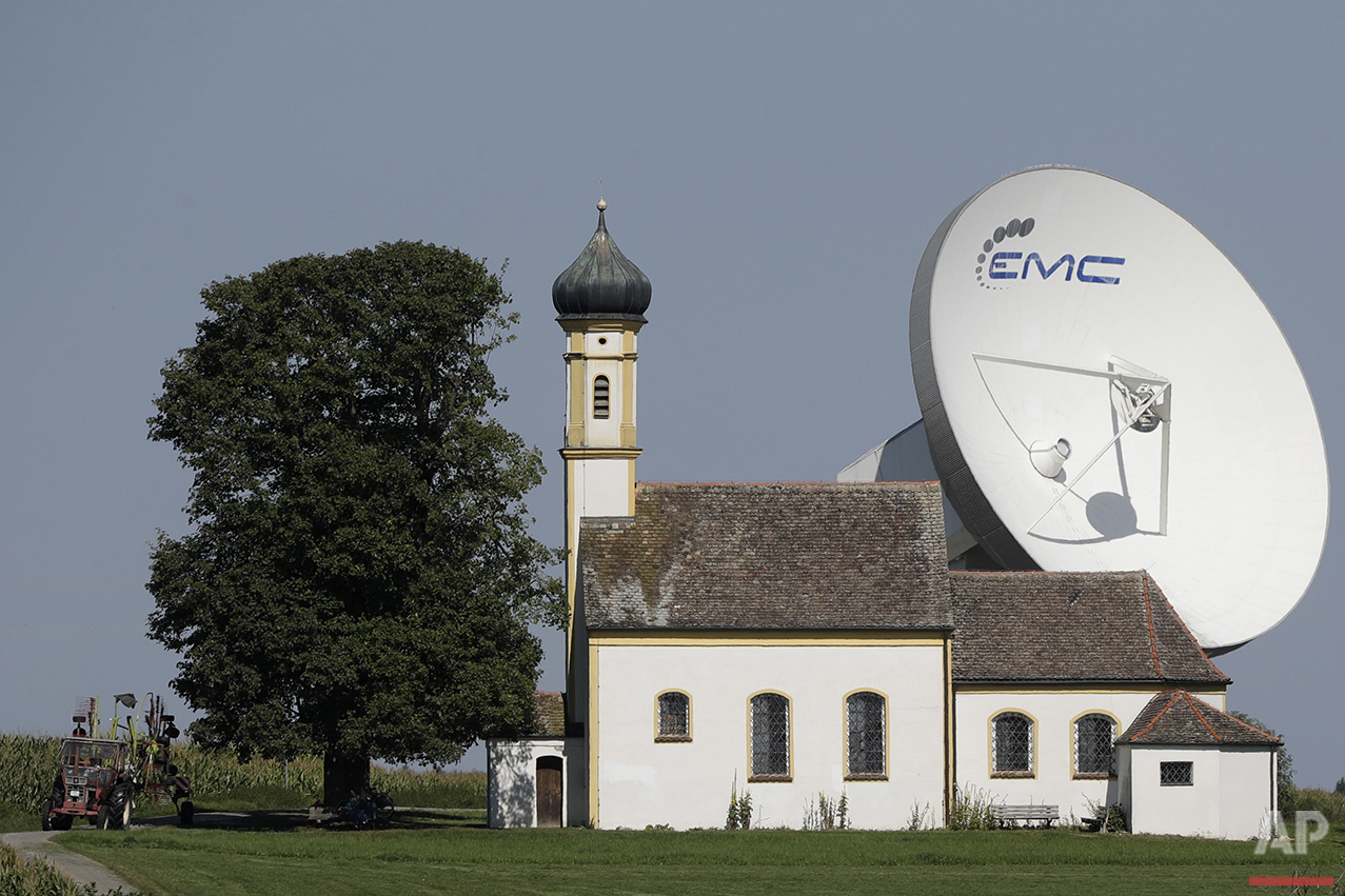 A farmer drives his tractor in front of a parabolic antenna and the Baroque church of Saint John in Raisting near Weilheim, Germany, Thursday, Sept. 8, 2016. (AP Photo/Matthias Schrader)
