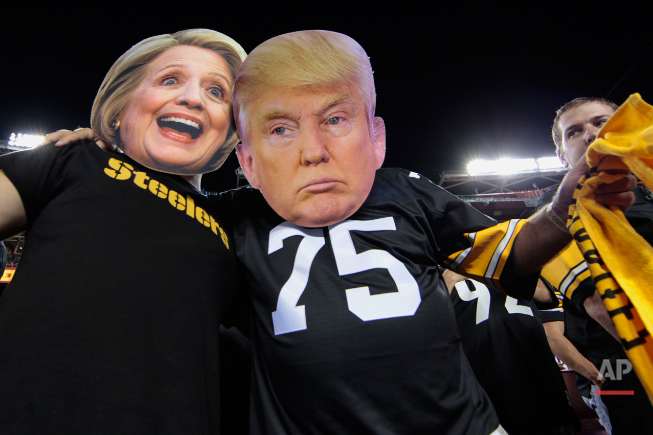 Pittsburgh Steelers fans Brian Picchini (left) and Rusty Kuchta (right) wear presidential candidates Sec. Hillary Clinton and Donald J. Trump masks during the first half of an NFL football game against the Washington Redskins in Landover, Md., Monday, Sept. 12, 2016. (AP Photo/Mark Tenally)