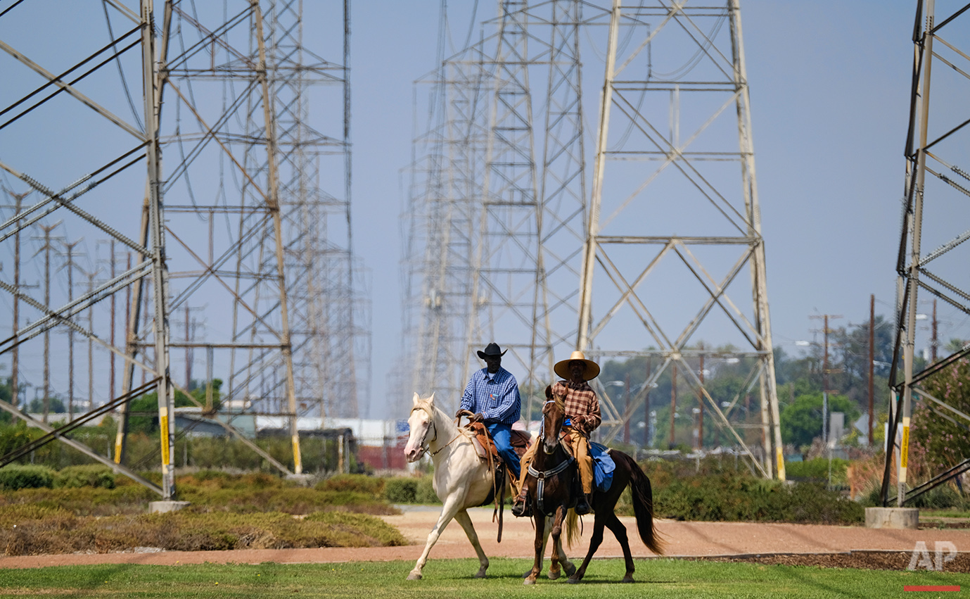 Ivory McCloud, left, and his friend, Mike Jones, ride along a path under power lines in Compton, Calif., Sunday, Aug. 7, 2016.  (AP Photo/Richard Vogel)