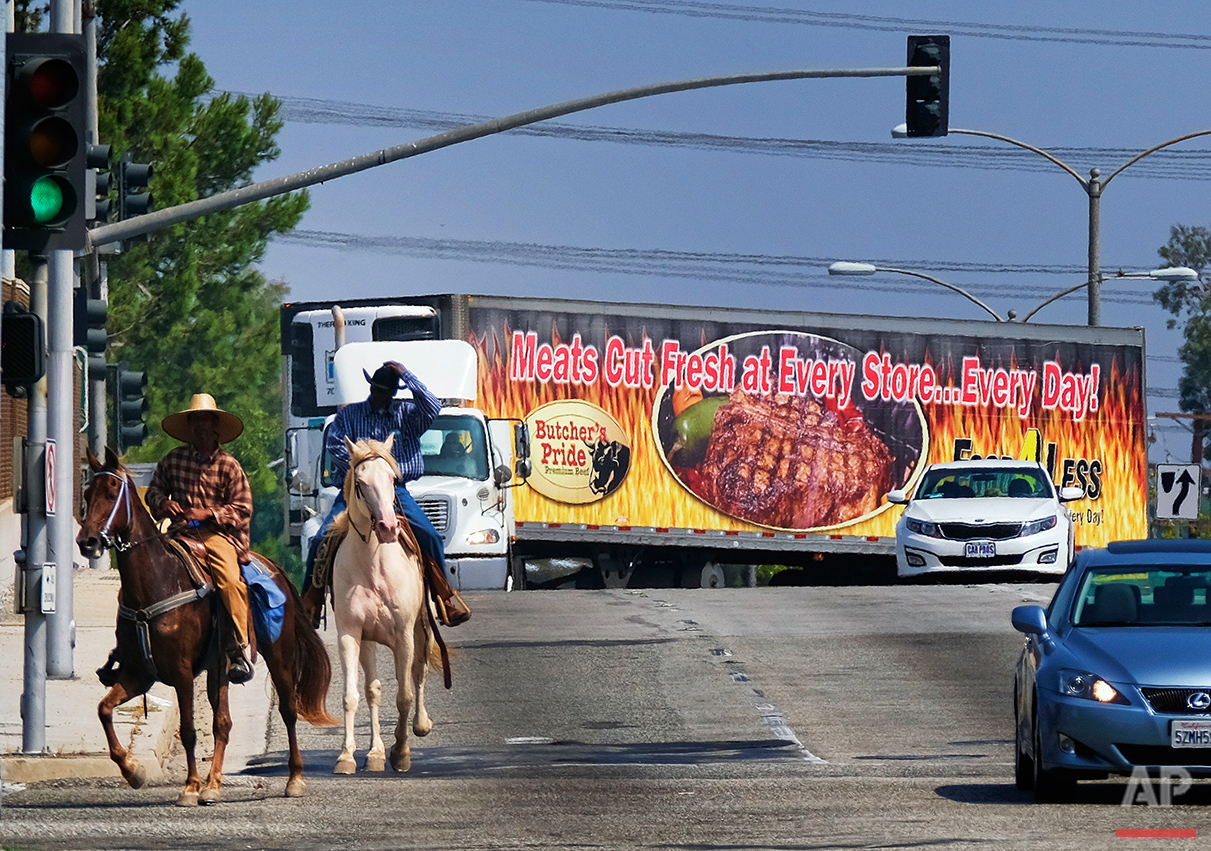 Ivory McCloud, right, and his friend, Mike Jones, ride their horses down a street in Compton, Calif., on Sunday, Aug. 7, 2016. Although best known as the birthplace of gangsta rap and the hometown of tennis superstars Venus and Serena Williams, Compton has a long and vibrant equestrian history. (AP Photo/Richard Vogel)