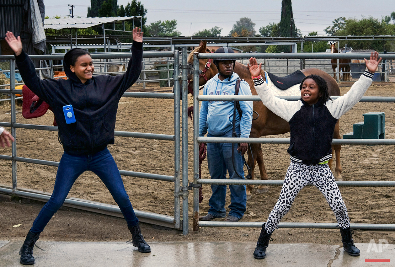 Neighborhood kids exercise before riding horses in the Compton Junior Posse Youth Equestrian Program in Compton, Calif., on Saturday, June 6, 2016. Mayisha Akbar, who moved here with her family almost 30 years ago, put her three children on horses to keep them out of trouble, and soon she found other kids wanted to ride with them. So she formed the Compton Jr. Posse and began teaching riding. (AP Photo/Richard Vogel)