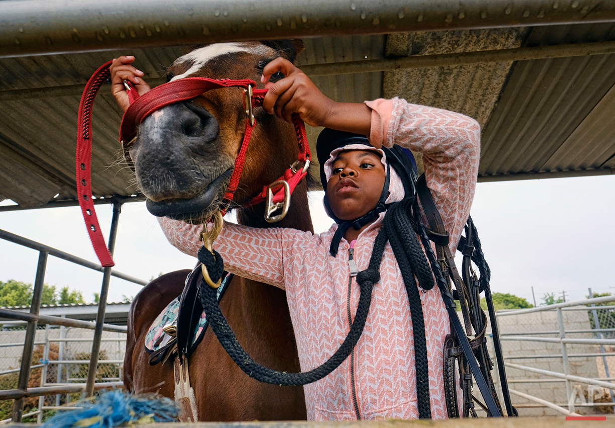 Adrina Player, 9, places a lead on a horse at the Compton Junior Posse Youth Equestrian Program in Compton, Calif., on Saturday, June 6, 2016. Mayisha Akbar, who moved here with her family almost 30 years ago, put her three children on horses to keep them out of trouble, and soon she found other kids wanted to ride with them. So she formed the Compton Jr. Posse and began teaching riding. (AP Photo/Richard Vogel)