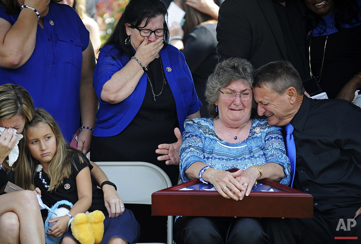Emily and John Garafola, right, parents of fallen East Baton Rouge Sheriff deputy Brad Garafola, weep after being presented with a flag during funeral services for their son in Baton Rouge, La., Saturday, July 23, 2016. Brad Garafola, slain by a gunman who authorities said targeted law enforcement, was one of three officers killed. (Hilary Scheinuk/Baton Rouge Advocate via AP, Pool)