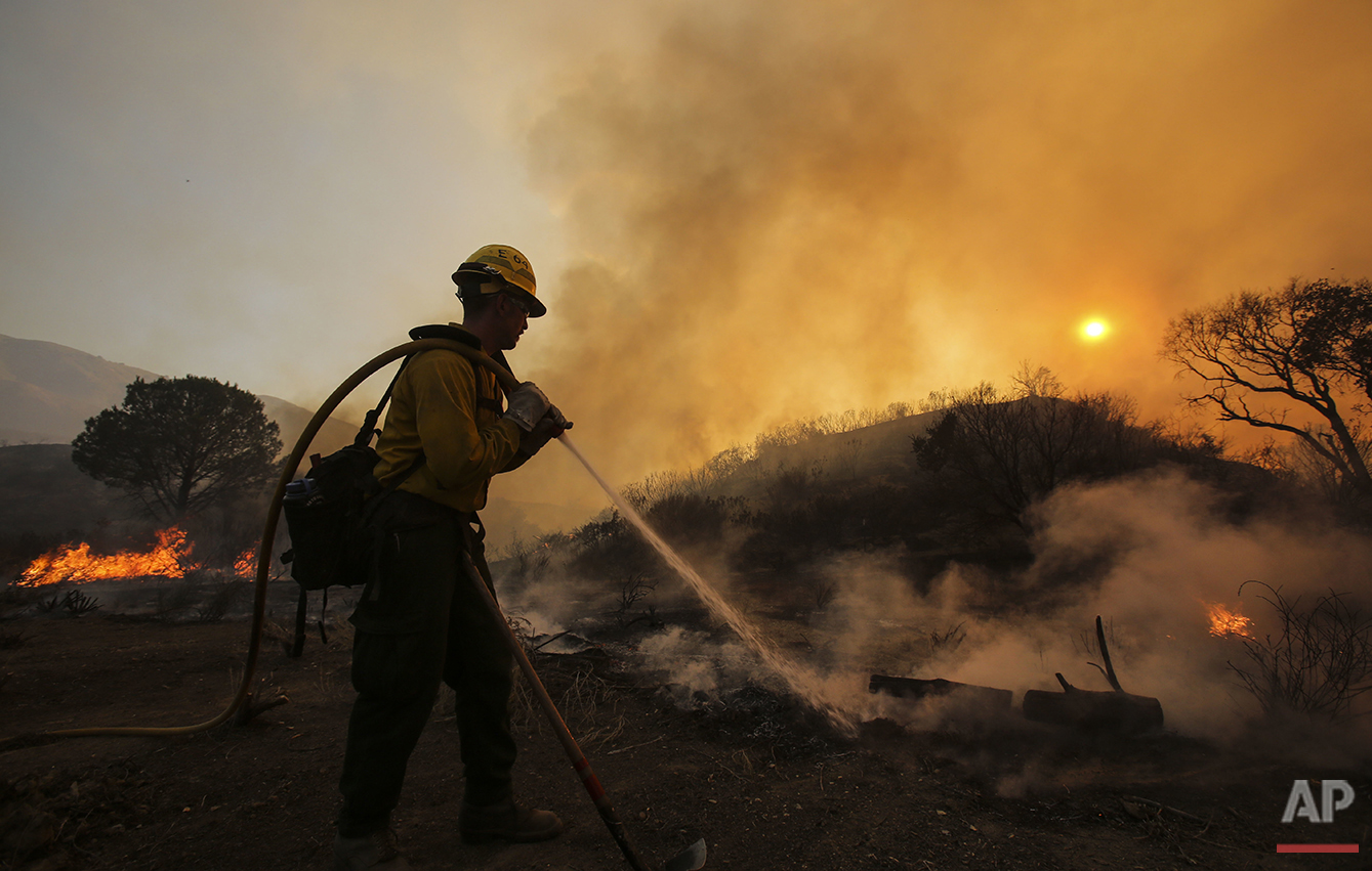 A firefighter battles a wildfire near Placerita Canyon Road in Santa Clarita, Calif., Sunday, July 24, 2016. Thousands of homes remained evacuated Sunday as two massive wildfires raged in tinder-dry California hills and canyons. (AP Photo/Ringo H.W. Chiu)