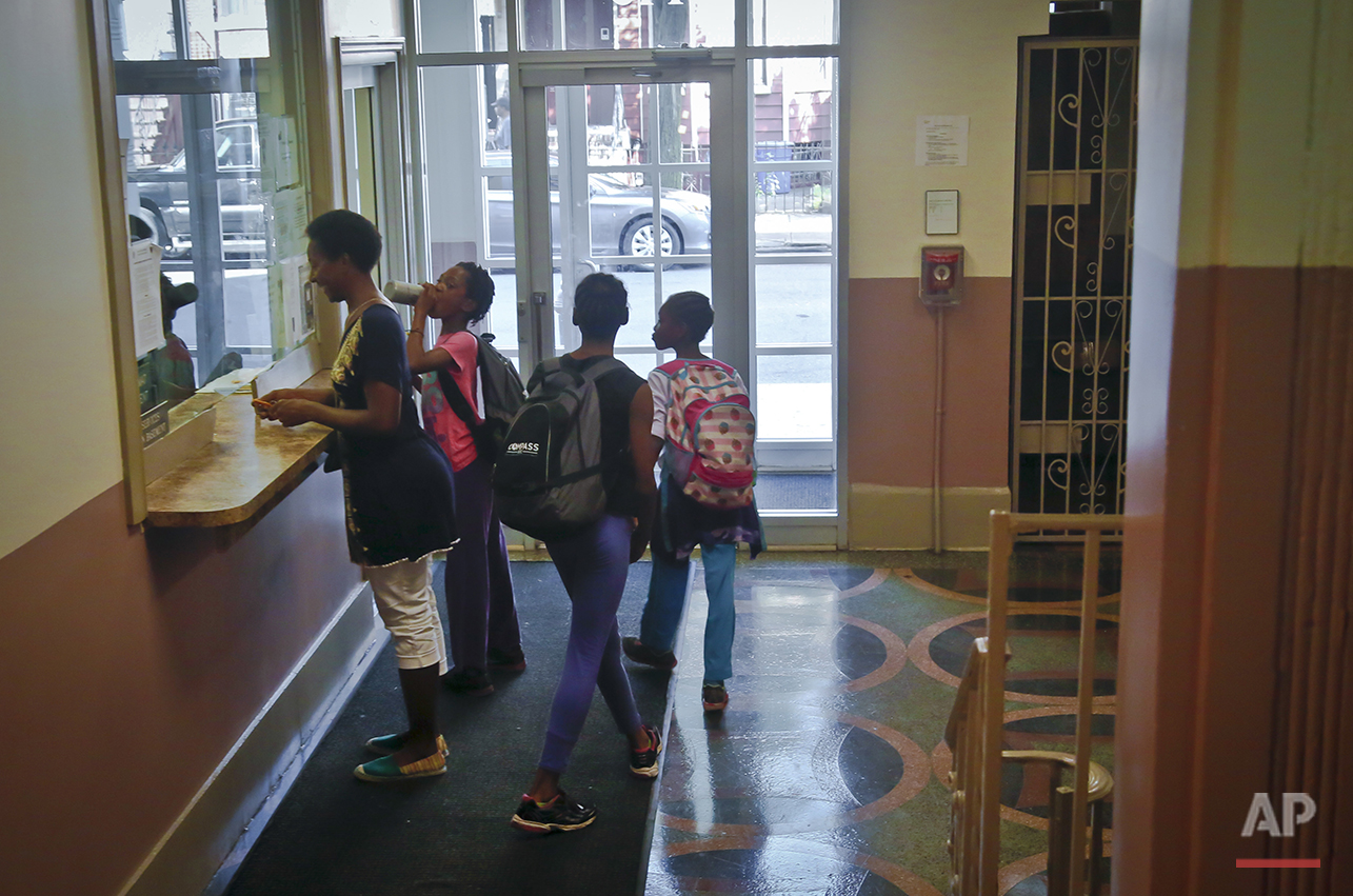 "In this Wednesday, July 20, 2016 photo, Tonia Handy, far left, and her daughters, Rainn Sheppard, 10, second from left, Tai Sheppard, 11, second from right, and Brooke Sheppard, 8, far right, prepare to leave their a Brooklyn shelter for track practice, in New York. The sisters have only been running track and field for a year and a half, but already rank at the top of their field. ""They're some of the best athletes in the country in their age groups,"" said their coach Jean Bell of the Jeuness Track Club. ""For the upcoming junior Olympics in Houston we expect for them to bring home many, many medals and that's not an easy feat."" (AP Photo/Bebeto Matthews)"
