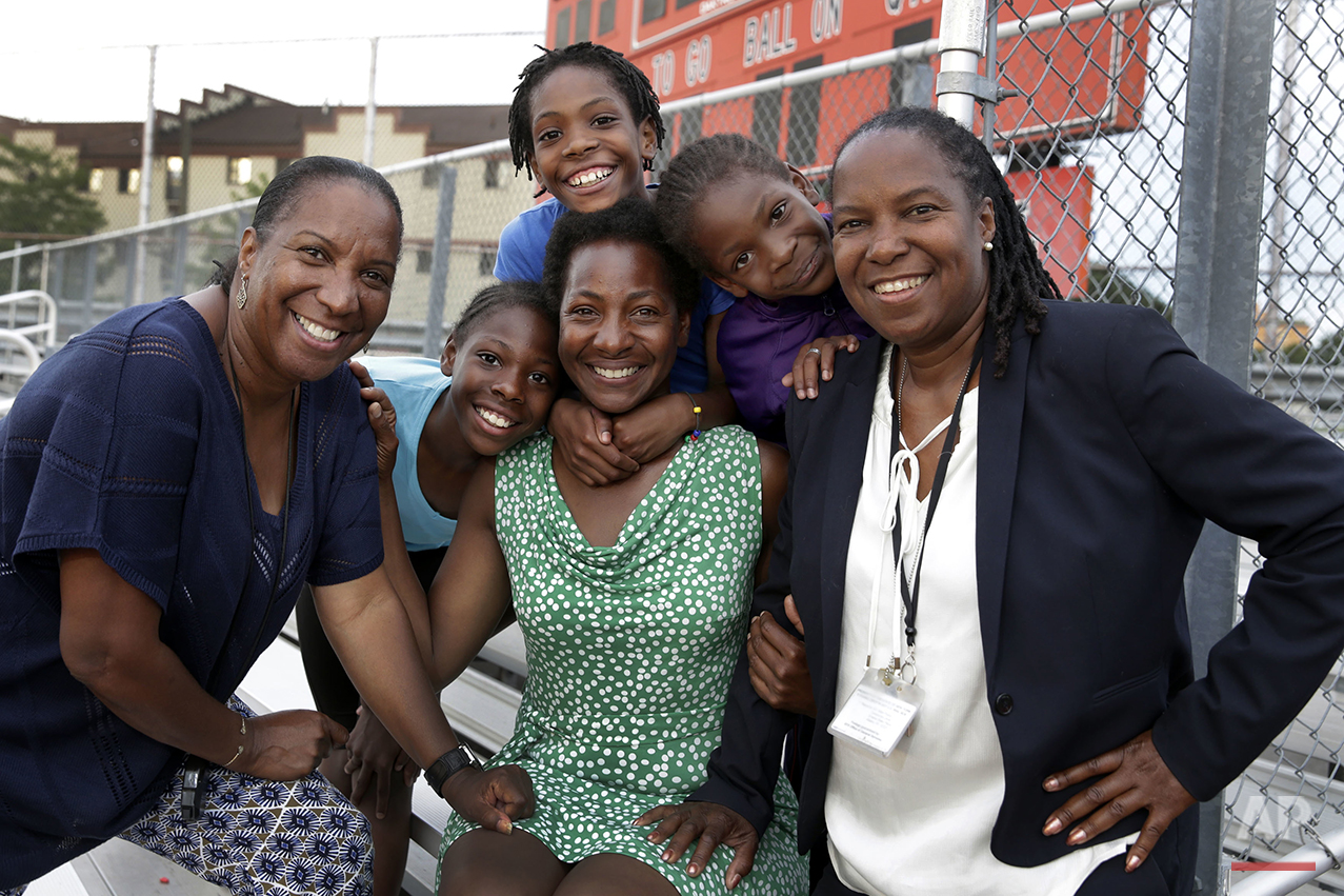 In this July 11, 2016 photo, Tonia Handy, 46, seated center, is surrounded by her children, Tai Sheppard, 11, Rainn Sheppard, 10, and Brooke Sheppard, 8, left to right, and flanked by coaches Karel Lancaster, left, and Jean Bell, right, after track workouts at Boys and Girls High School, in Brooklyn borough of New York. Every morning, the three young sisters wake up together with their mom in one bed in a Brooklyn homeless shelter. Every afternoon, they train in a sport that they hope will put them on a path to a better life. The girls have blossomed since taking up track and field just a year and a half ago, and earned top youth track rankings and a spot in this week's Junior Olympics. (AP Photo/Richard Drew)