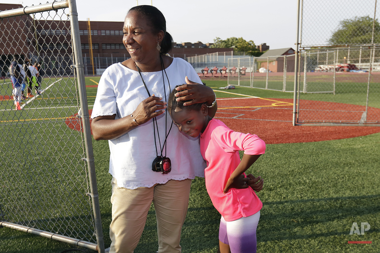 In this July 12, 2016 photo, Brooke Sheppard, 8, is hugged by one of her coaches Karel Lancaster, during training at Boys and Girls High School in the Brooklyn borough of New York. Every morning, Brooke and her two young sisters wake up together with their mom in one bed in a Brooklyn homeless shelter. Every afternoon, they train in a sport that they hope will put them on a path to a better life. The girls have blossomed since taking up track and field just a year and a half ago, and earned top youth track rankings and a spot in this week's Junior Olympics. (AP Photo/Richard Drew)
