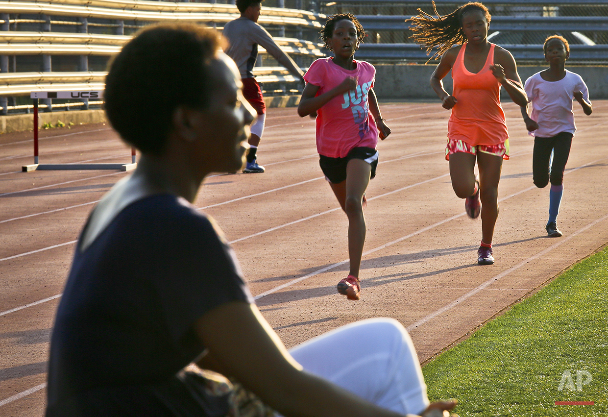 "In this Wednesday, July 20, 2016 photo, Tonia Handy, far left, sits near the track during an interview as her daughters Rainn Sheppard, 10, second from left, and Brooke Sheppard, 8, far right, run during track practice at Boys and Girls High School in the Brooklyn borough of New York. Rainn, Brooke and their older sister Tai, 11, live in a New York City homeless shelter with Handy, yet have earned top youth track rankings and a spot in this week's Junior Olympics. ""I want their dreams to come true. And I want them to be a part of it in making it happen,"" said Handy. ""And hard work is something they are learning right here everyday on the track."" (AP Photo/Bebeto Matthews)"