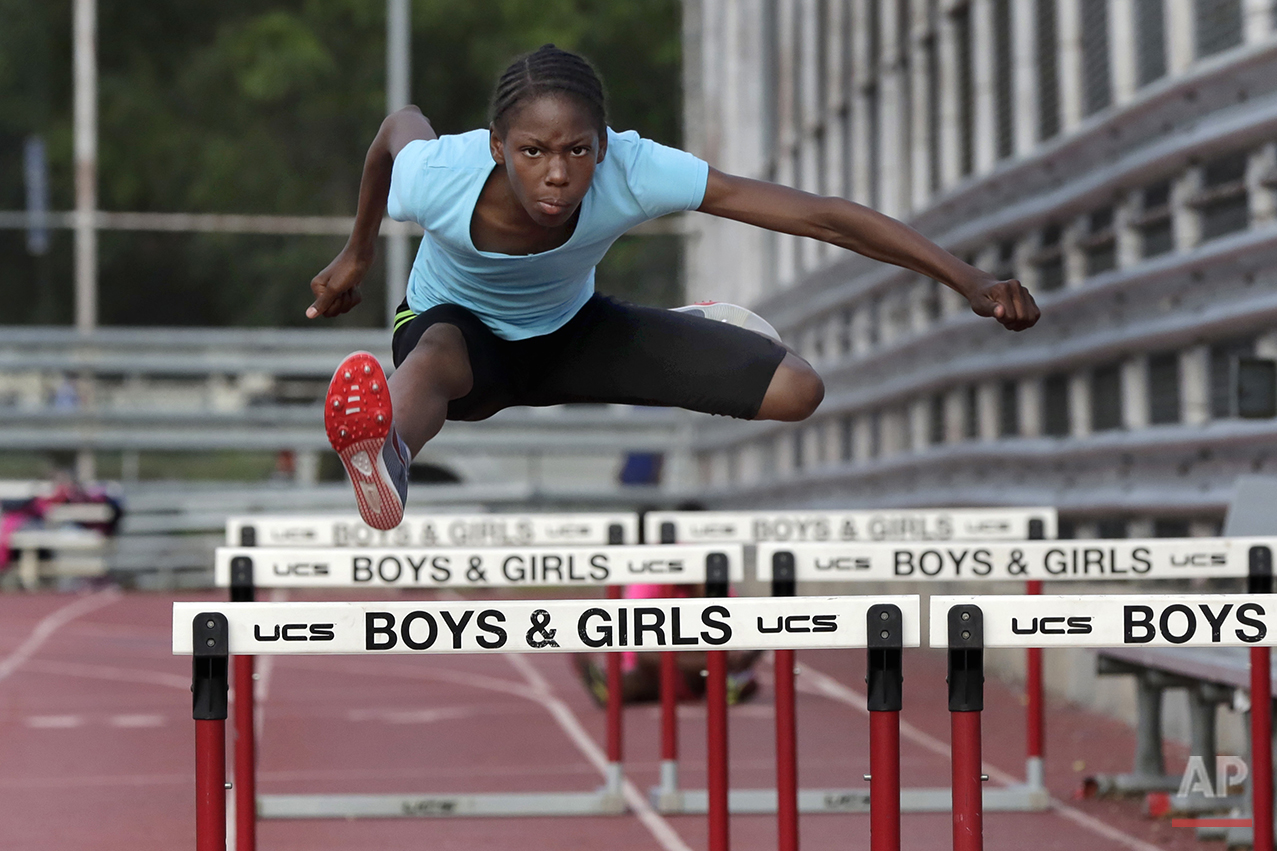 In this July 11, 2016 photo, Tai Sheppard, 11, practices hurdles at Boys and Girls High School, in the Brooklyn borough of New York. Every morning, Tai and her two young sisters wake up together with their mom in one bed in a Brooklyn homeless shelter. Every afternoon, they train in a new found sport that they hope will put them on a path to a better life. The girls have blossomed since taking up track and field just a year and a half ago, rising to the top tier of their national age-group rankings and earning a spot in the Junior Olympic Games, now underway in Houston. (AP Photo/Richard Drew)