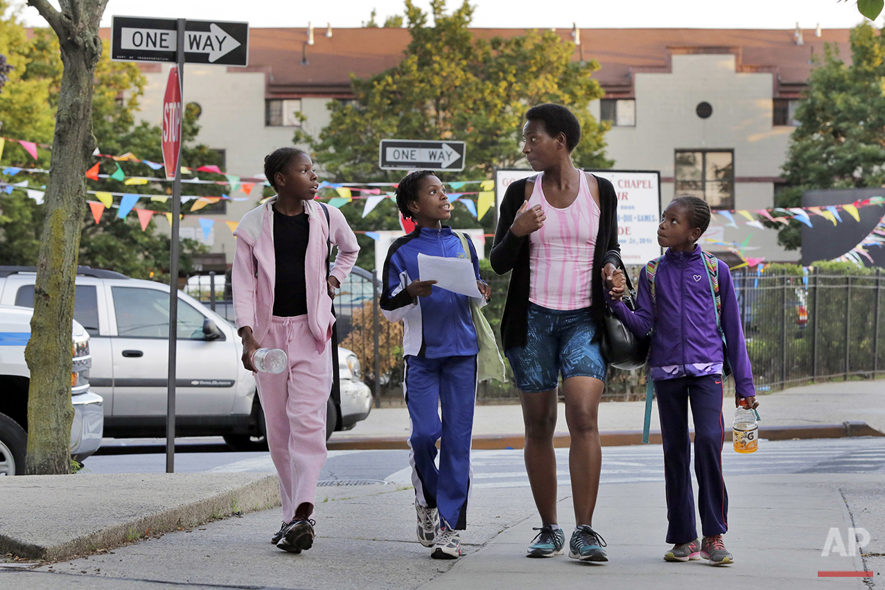 In this July 12, 2016 photo, Tonia Handy, 46, is surrounded by her children, Tai Sheppard, 11, Rainn Sheppard, 10, and Brooke Sheppard, 8, left to right, walk home after track workouts at Boys and Girls High School, in the Brooklyn borough of New York. Every morning, three young sisters wake up together with their mom in one bed in a Brooklyn homeless shelter. Every afternoon, they train in a sport that they hope will put them on a path to a better life. The girls have blossomed since taking up track and field just a year and a half ago, and earned top youth track rankings and a spot in this week's Junior Olympics. (AP Photo/Richard Drew)