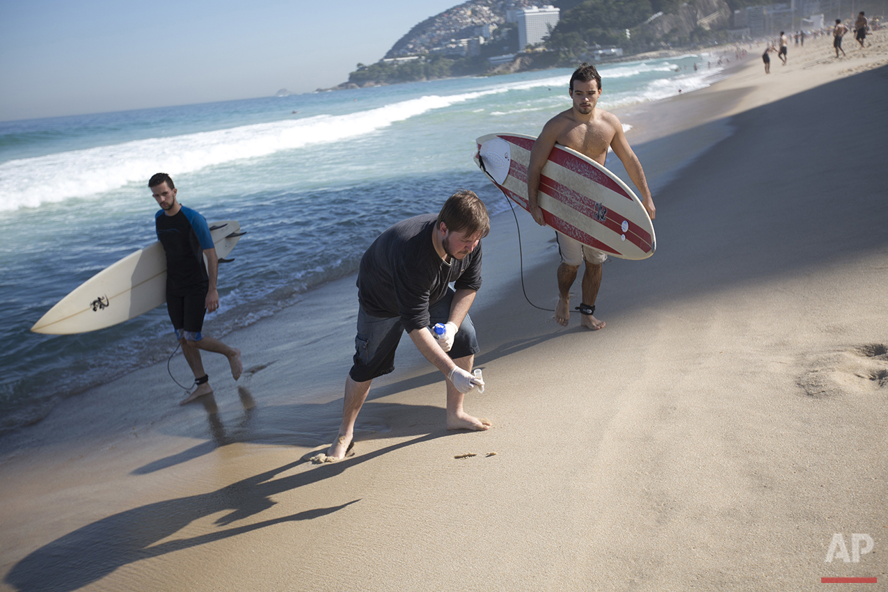 In this July 11, 2016 photo, doctoral candidate Rodrigo Staggemeier collects samples of sand from Ipanema beach, for a study commissioned by The Associated Press, in Rio de Janeiro. The 16-month study has shown that the city's beaches, lagoons and other waterways are polluted with astronomical amounts of human sewage, putting at risk the health of Olympic athletes and visitors to Rio's showcase beaches. (AP Photo/Silvia Izquierdo)
