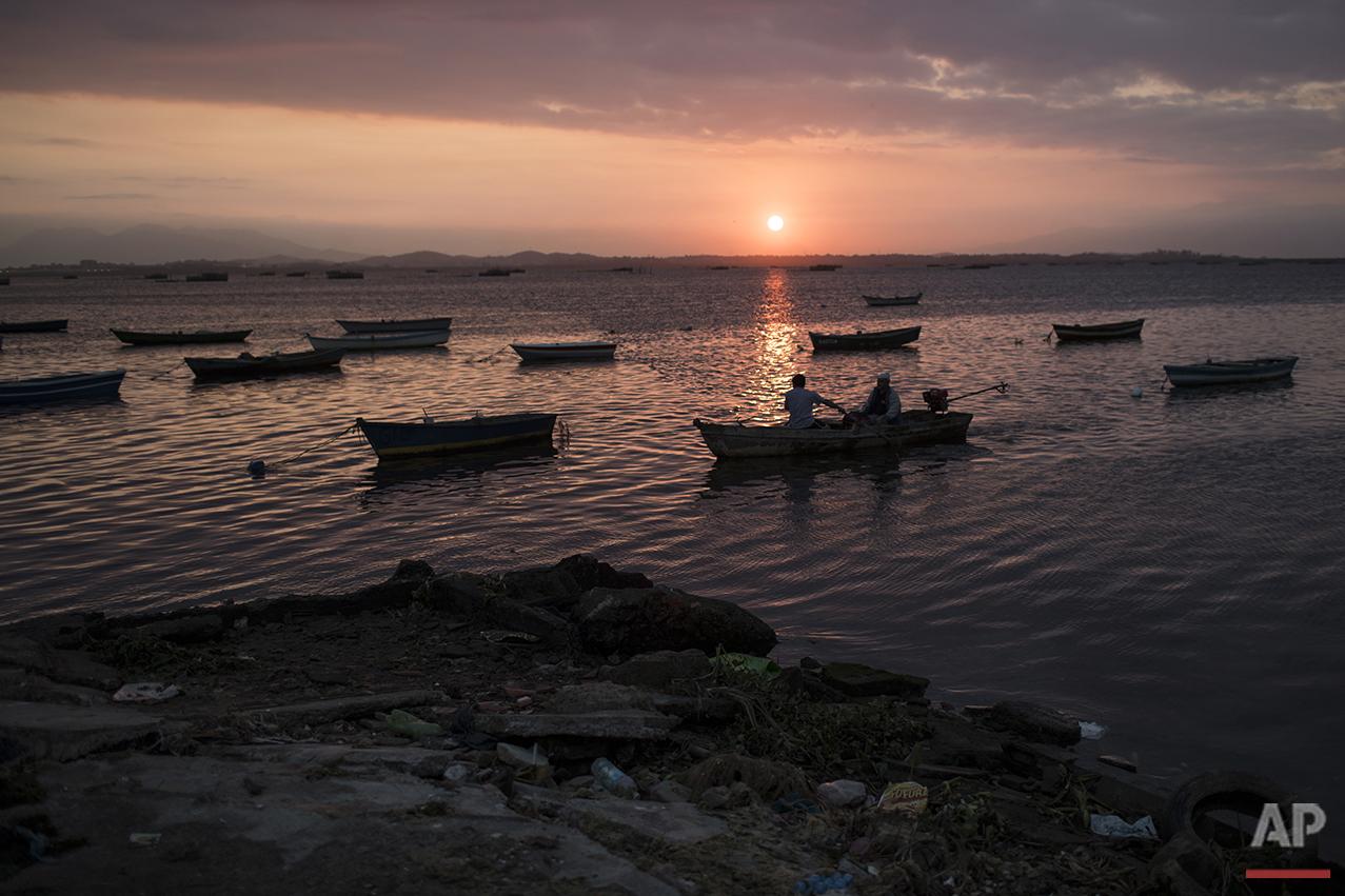 Fishermen park their boat near a polluted shore in Guanabara bay in Rio de Janeiro, Saturday, July 30, 2016. (AP Photo/Felipe Dana)