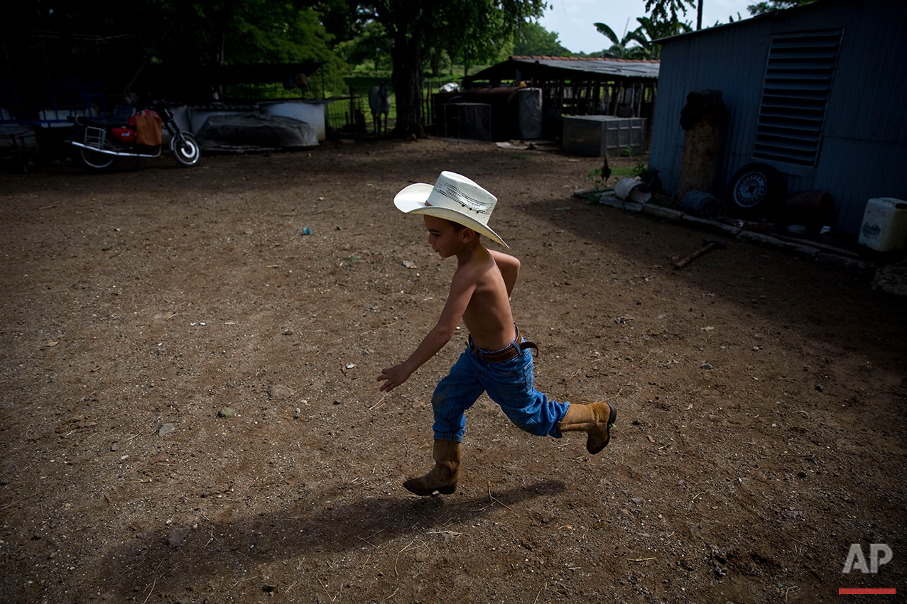 In this July 29, 2016 photo, 5-year-old cowboy David Obregon runs across the yard of his parents farm in Sancti Spiritus, central Cuba. In the Cuban countryside, many children learn to ride a horse before they learn to ride a bicycle. Those who grow up to be the best start farm- and ranch-related studies at local universities without passing the difficult national entrance exam. (AP Photo/Ramon Espinosa)