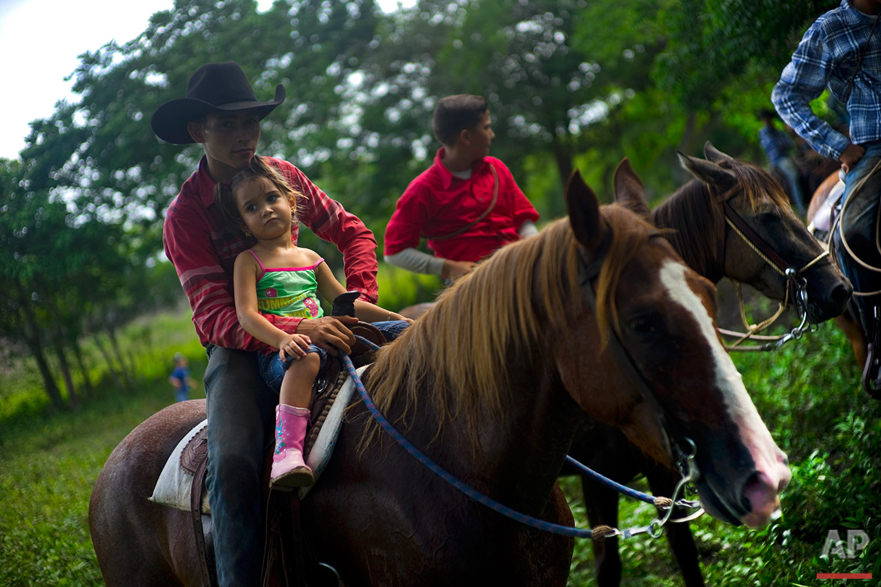 In this July 29, 2016 photo, cowboys watch an improvised rodeo event at a farm in Sancti Spiritus, central Cuba. In the Cuban countryside, many children learn to ride a horse before they learn to ride a bicycle. (AP Photo/Ramon Espinosa)