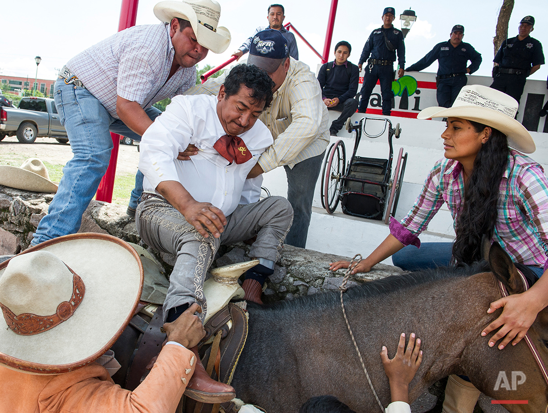 In this July 10, 2016 photo, charro or Mexican cowboy Salvador Espinoza mounts his horse, with the aid of rodeo hands, at the Mexican rodeo arena in Cuautitlán Izcalli, Mexico. In the traditional Mexican sport of charreria, this country's version of rodeo, they say you have to be agile, tough and brave. For Espinoza and other members of the Mexican Association of Paracharreria and Equestrian Therapy, it also means competing with amputations, partial blindness, deafness or paralysis in the same daredevil events as their more able-bodied peers: lassoing, horse-reining, bull-riding and others. (AP Photo/Nick Wagner)