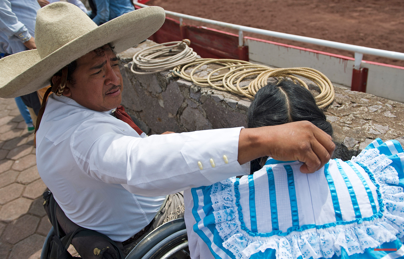 "In this July 10, 2016 photo, charro Salvador Espinoza fixes the collar of his wife Graciela Sanchez Martinez, dressed in her escaramuza outfit, as they prepare to mount horses at a Mexican rodeo arena in Cuautitlán Izcalli, Mexico. ""This is where I have learned that athletes in wheelchairs have no limits,"" said Espinoza, who lost use of his legs 16 years ago when he fell from a four-story building while installing air conditioners. ""The only limit is the one people give themselves."" (AP Photo/Nick Wagner)"