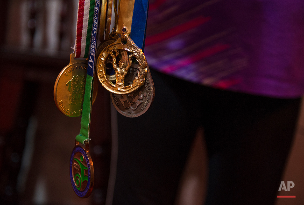 In this July 21, 2016 photo Graciela Sanchez Martinez shows off a collection of Para-rodeo and basketball medals garnered by her husband Salvador Espinoza over 10 years ago, at their home in Chalco, Mexico. Sanchez Martinez and her husband, who met over  10 years ago at a wheelchair basketball tournament, have performed in over a dozen charreadas and form the only married couple in the Patino paracharreria team. Sanchez Martinez was diagnosed at age 2 with Guillain-Barre syndrome, a nerve disorder that can cause muscle weakness and sometimes paralysis. (AP Photo/Nick Wagner)