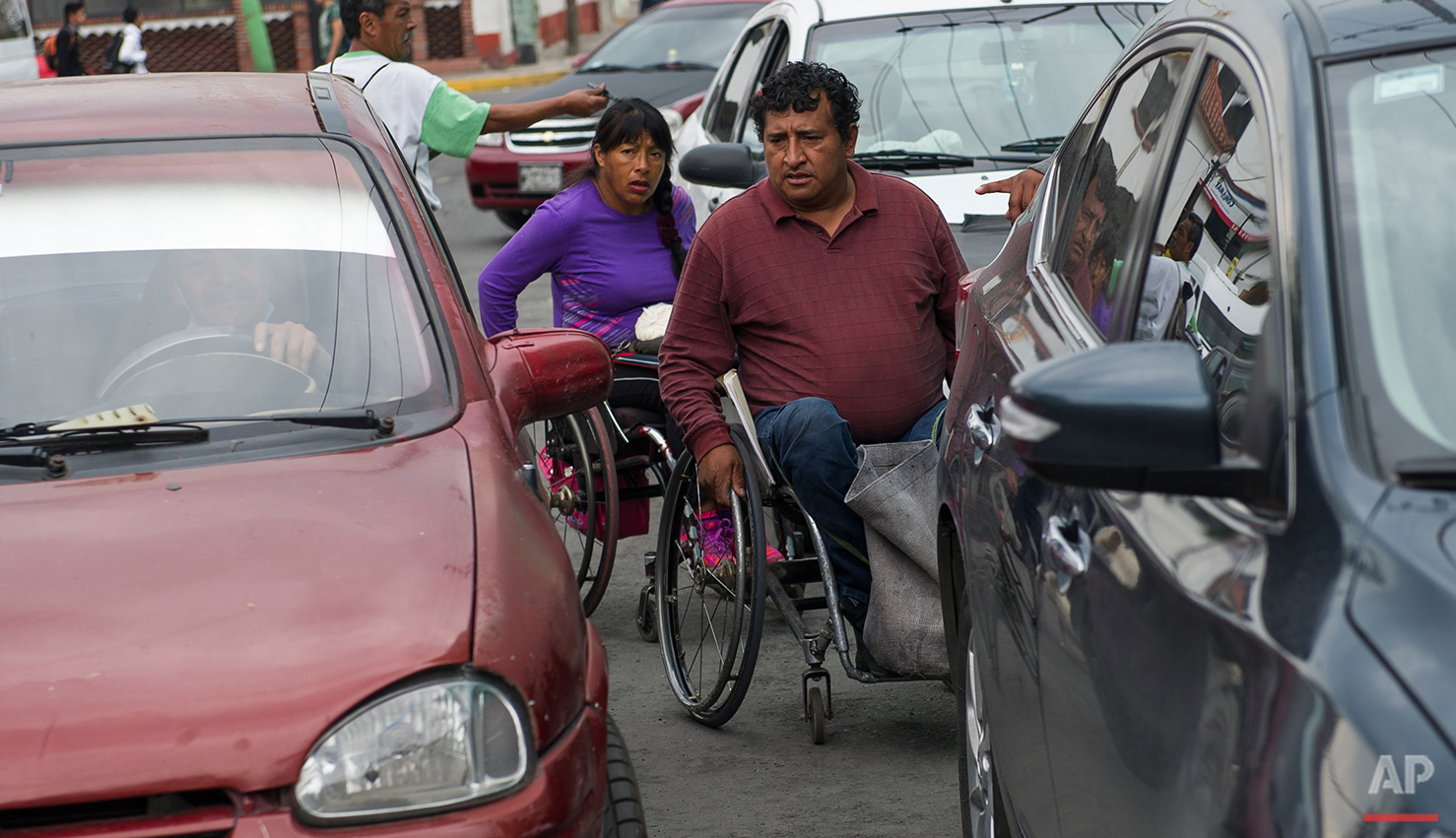 In this July 21, 2016 photo, Salvador Espinoza and Graciela Sanchez Martinez maneuver through traffic while selling sugar in Chalco, Mexico. The couple sells sugar for 14 pesos, or about $0.75, as a way to earn a little more money in addition to the support they receive from the government. Espinoza and Sanchez Martinez, have performed in over a dozen charreadas and form the only married couple in the Patino paracharreria team. Sanchez Martinez was diagnosed at age 2 with Guillain-Barre syndrome, a nerve disorder that can cause muscle weakness and sometimes paralysis. A spinal cord injury left Espinoza paralyzed from the waist down. (AP Photo/Nick Wagner)