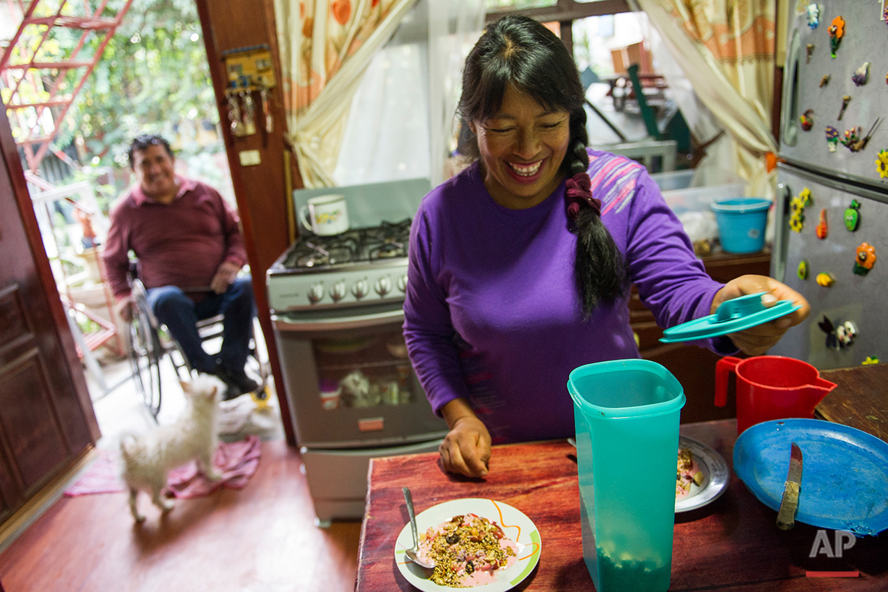 In this July 21, 2016 photo, Graciela Sanchez Martinez laughs with her husband, Salvador Espinoza, while preparing plates of yogurt and granola, at their home in Chalco, Mexico. Sanchez Martinez and her husband, who met over 10 years ago at a wheelchair basketball tournament, have performed in over a dozen charreadas and form the only married couple in the Patino paracharreria team. Sanchez Martinez was diagnosed at age 2 with Guillain-Barre syndrome, a nerve disorder that can cause muscle weakness and sometimes paralysis. (AP Photo/Nick Wagner)