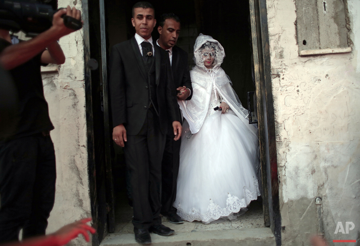 In this Saturday, July 31, 2016 photo, Palestinian groom Saed Abu Aser, 22, walks with his bride Falasteen, out of her family house to the wedding hall celebrating their wedding in Gaza City. Weddings in Gaza have emerged as a welcome celebration that slices through the often morose existence in the Gaza Strip. The coastal territory has been beaten down by three wars with Israel over the last decade and a stifling blockade imposed by Israel and Egypt. (AP Photo/ Khalil Hamra)