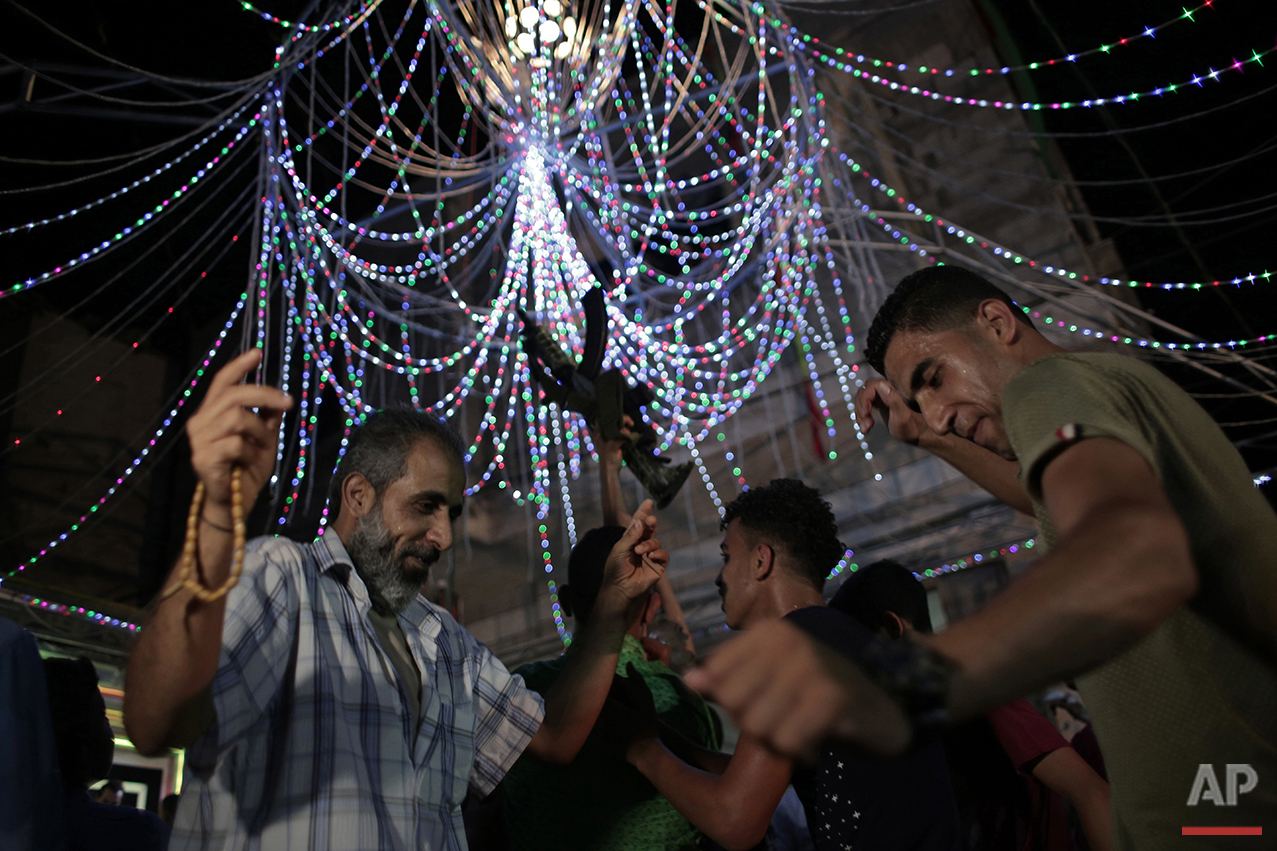 In this Thursday, July 29, 2016 photo, relatives of Palestinian groom Saed Abu Aser dance in a party celebrating his wedding in Gaza City. (AP Photo/ Khalil Hamra)
