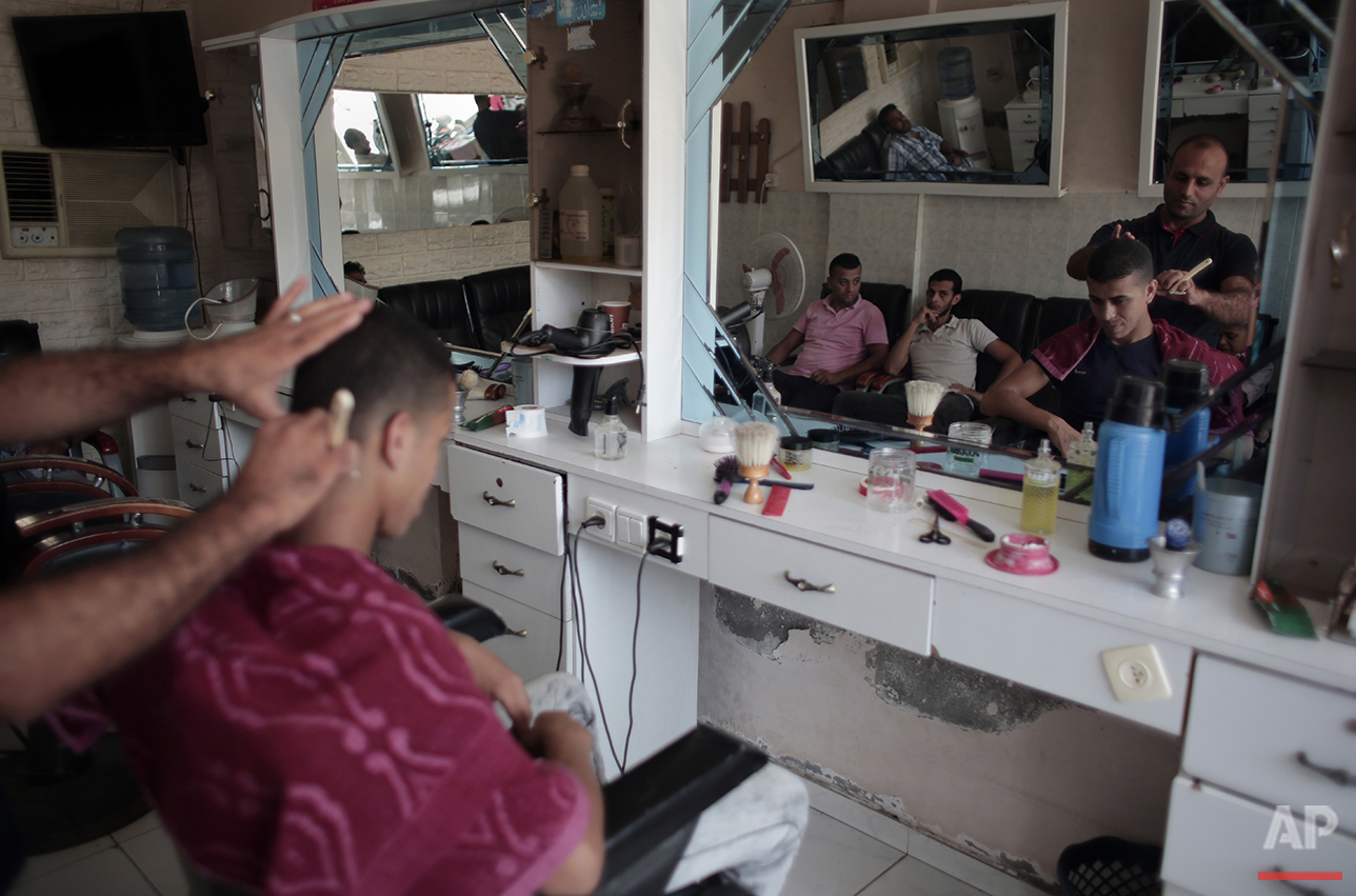 In this Saturday, July 31, 2016 photo, Palestinian groom Saed Abu Aser has a haircut while preparing himself for his wedding party in Gaza City. (AP Photo/ Khalil Hamra)