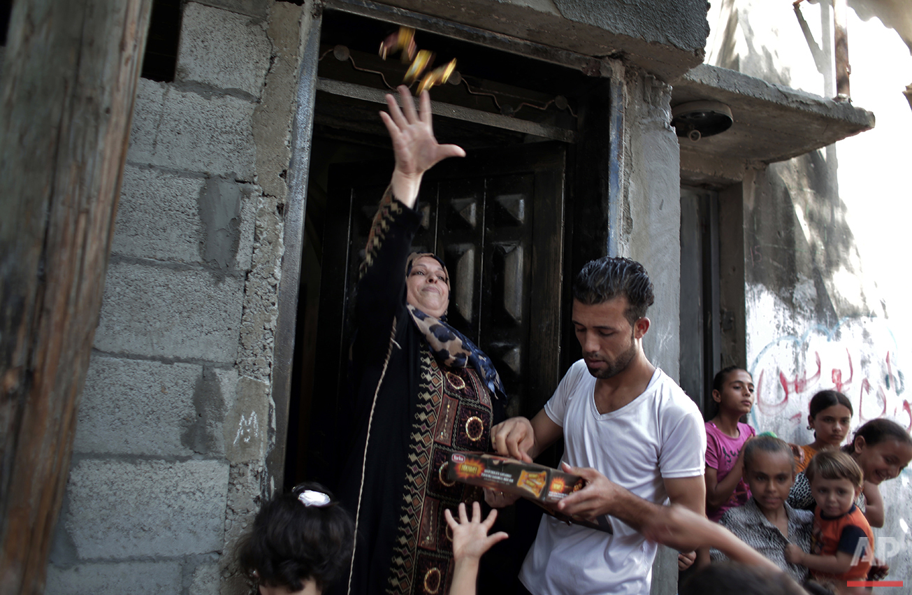 In this Saturday, July 31, 2016 photo, a woman throws candy as friends of Palestinian groom Saed Abu Aser carry him on their shoulders while dancing around the neighborhood before his wedding party in Gaza City. (AP Photo/Khalil Hamra)