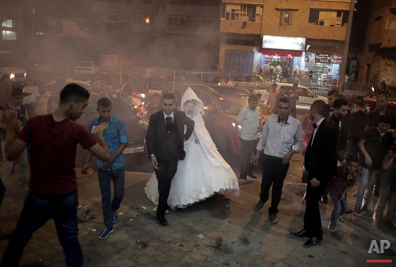 In this Saturday, July 31, 2016 photo, Palestinian groom Saed Abu Aser and his bride, Falasteen, walk into the wedding hall in Gaza City. (AP Photo/Khalil Hamra)