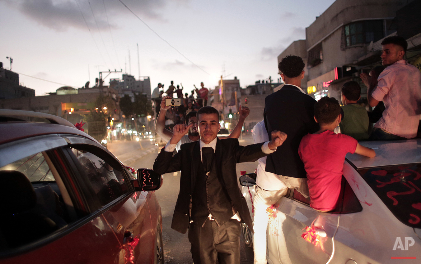 In this Saturday, July 31, 2016 photo, Palestinian groom Saed Abu Asers dances in the street on his way to the wedding hall in Gaza City. (AP Photo/Khalil Hamra)